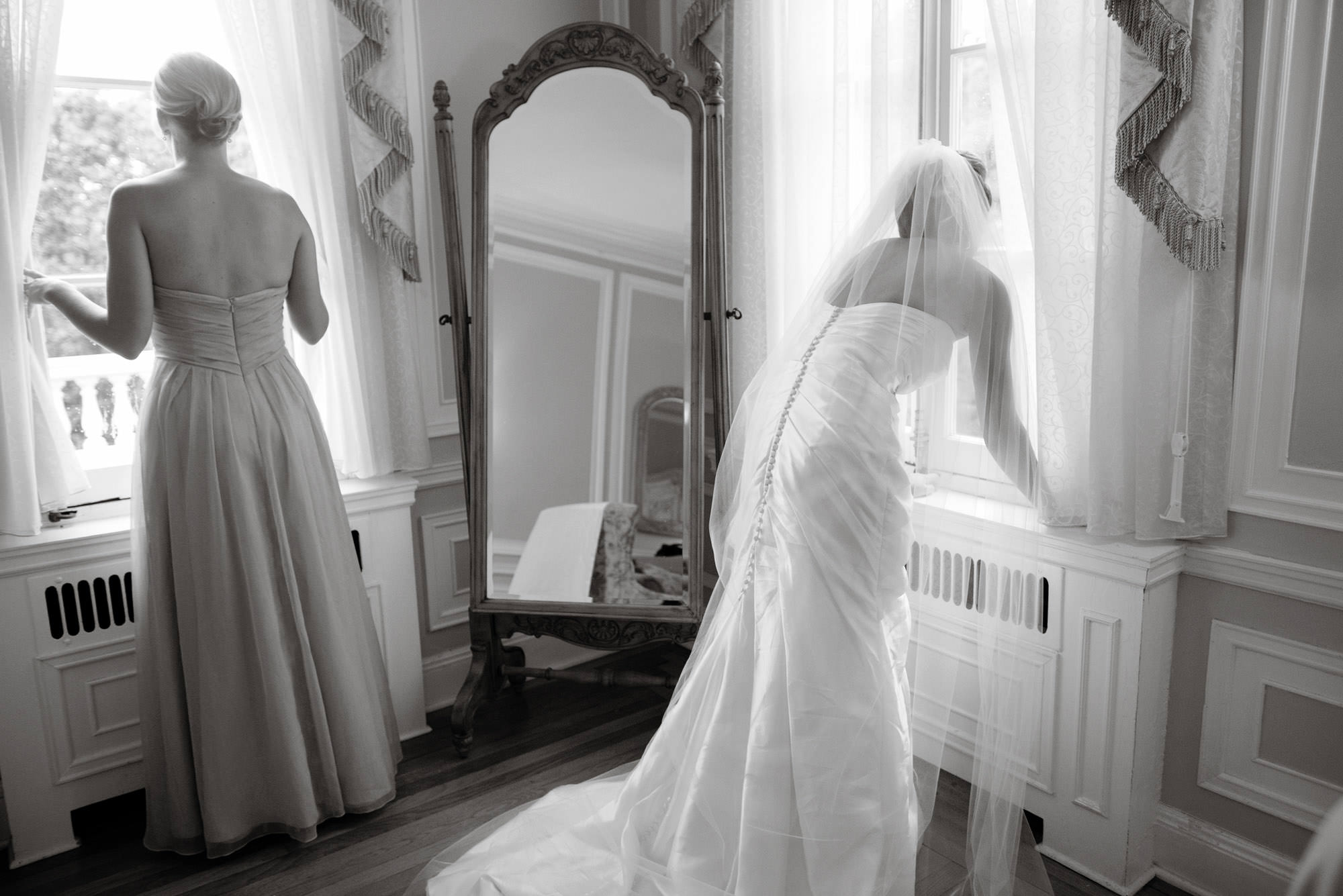 The bride looks out the window at her arriving guests on her Oxon Hill Manor wedding day.