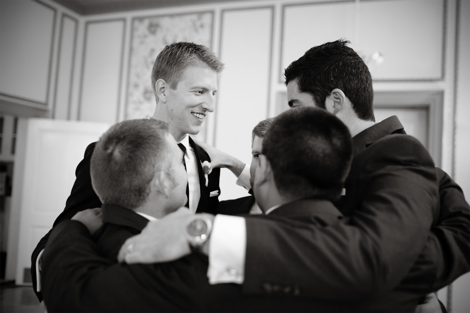 The groom huddles with his groomsmen on his Oxon Hill Manor wedding day.