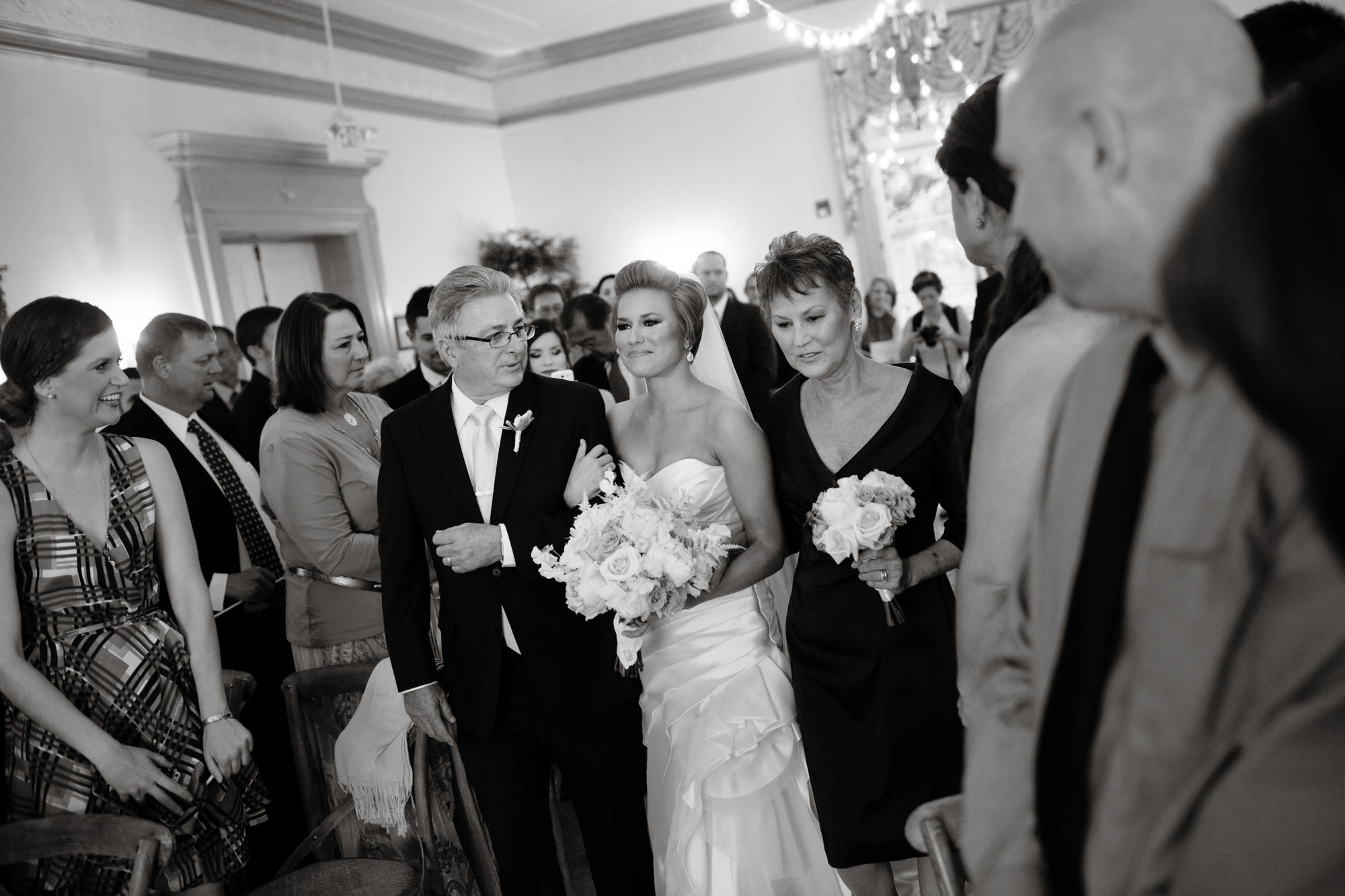 The bride is escorted down the aisle by her parents during the wedding ceremony at Oxon Hill Manor.