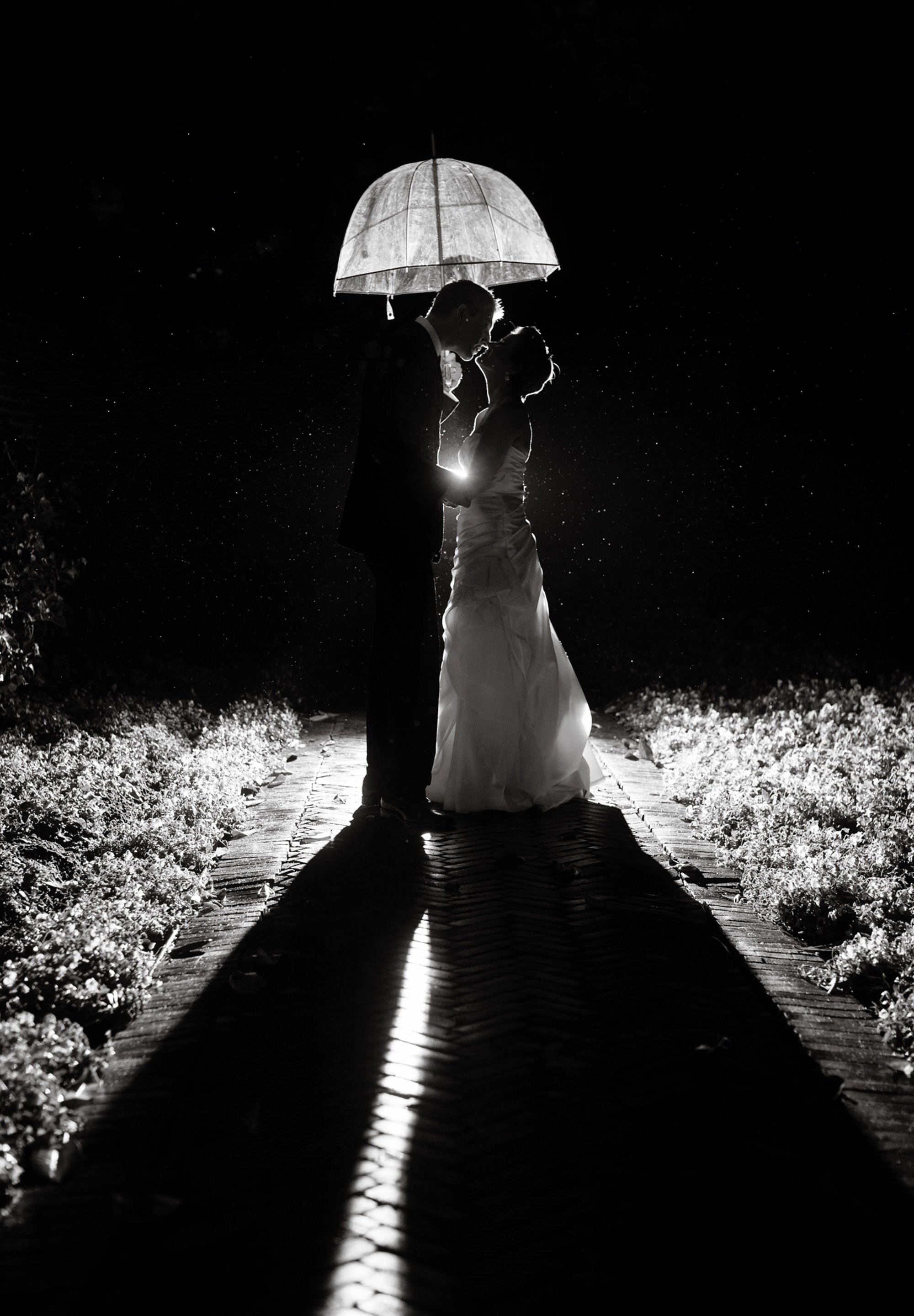 The bride and groom pose in the rain on their Oxon Hill Manor wedding day.