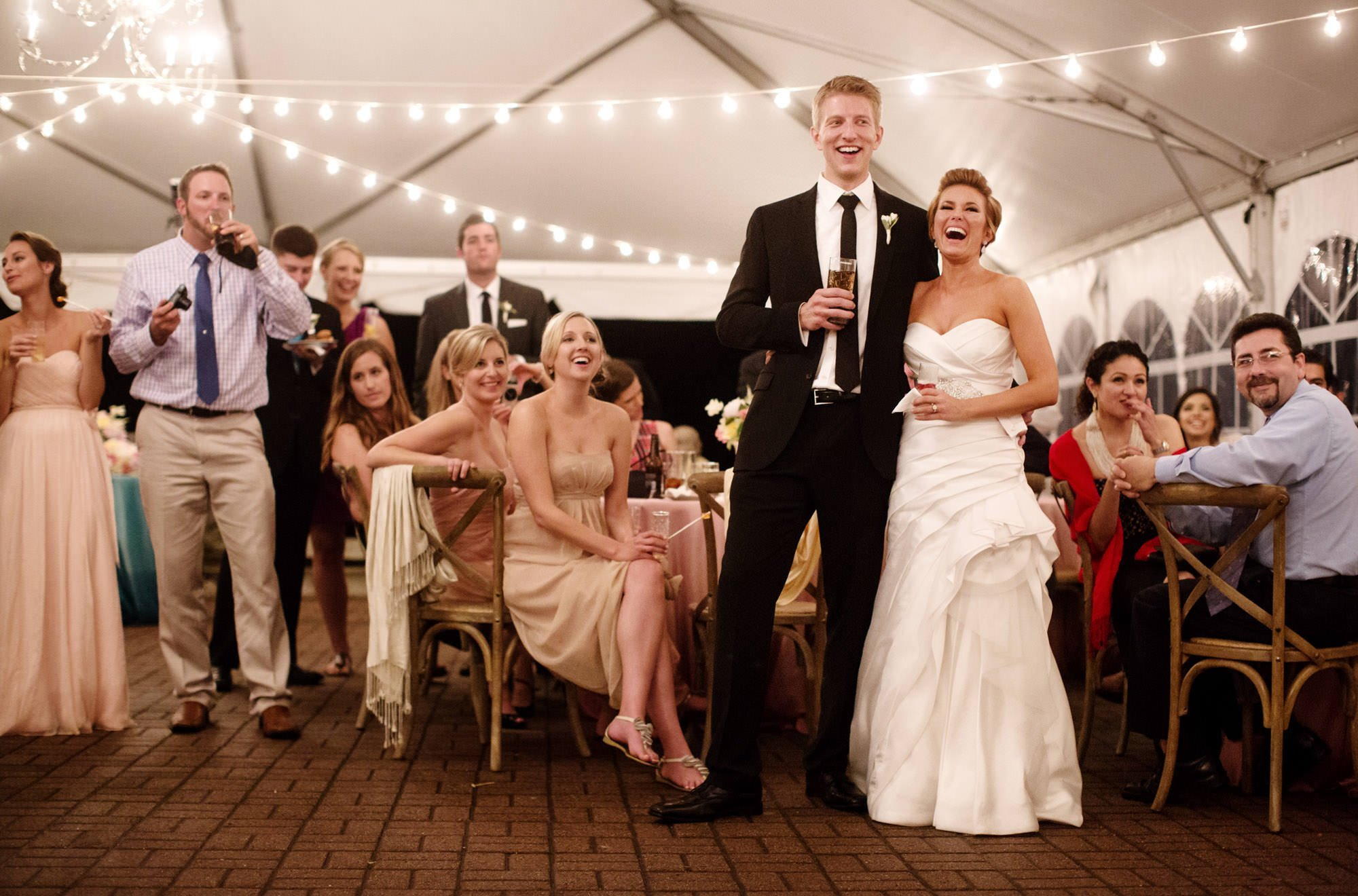 The bride and groom listen to toasts during the tented reception of their Oxon Hill Manor wedding.