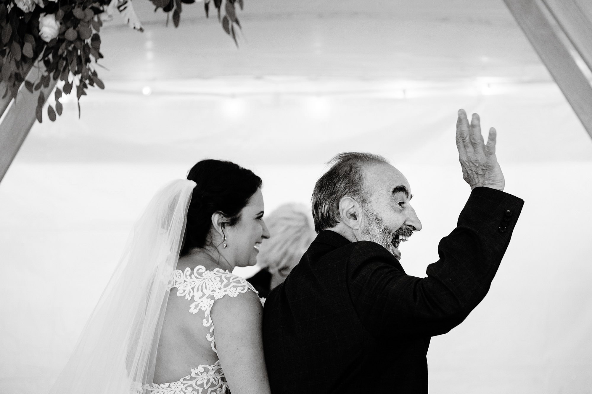 The father of the bride waves to guests during the wedding ceremony at Pelham House Resort.