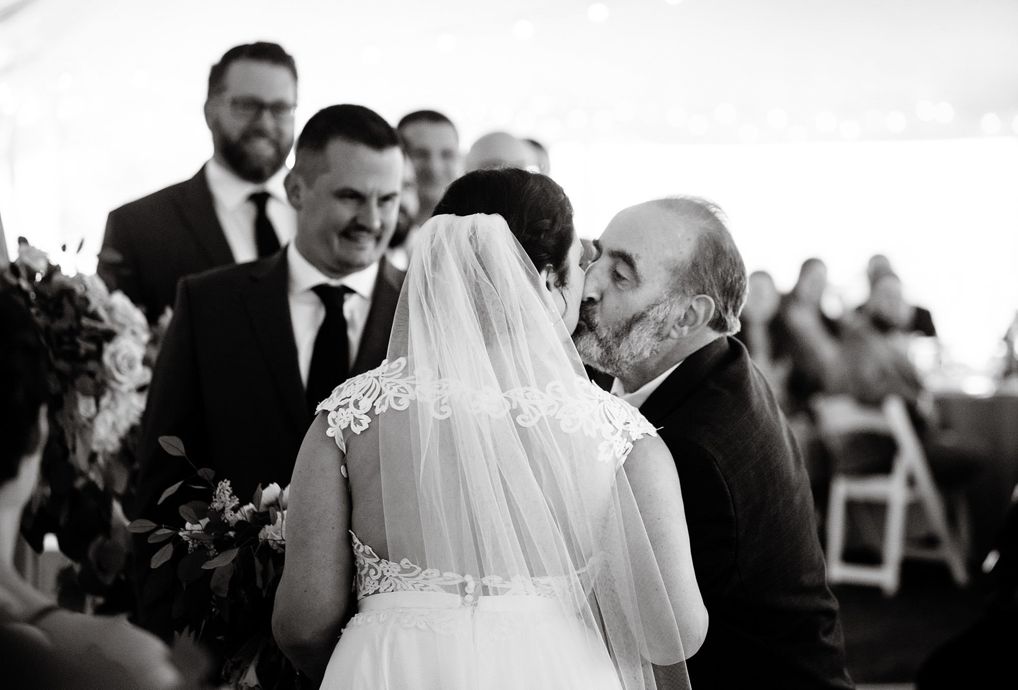 The father of the bride kisses his daughter during the ceremony.