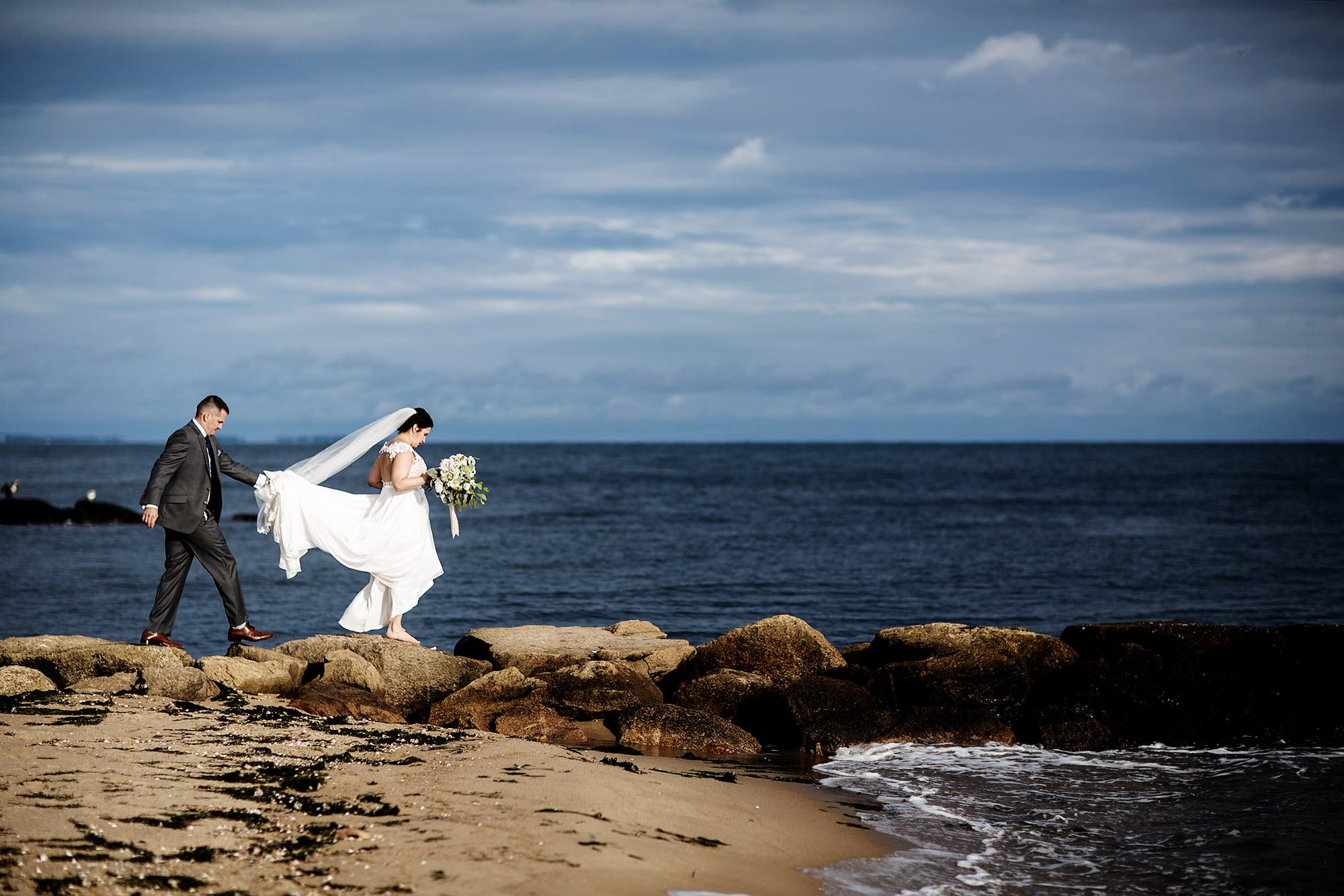 The bride and groom walk down the beach during their Pelham House Resort wedding.