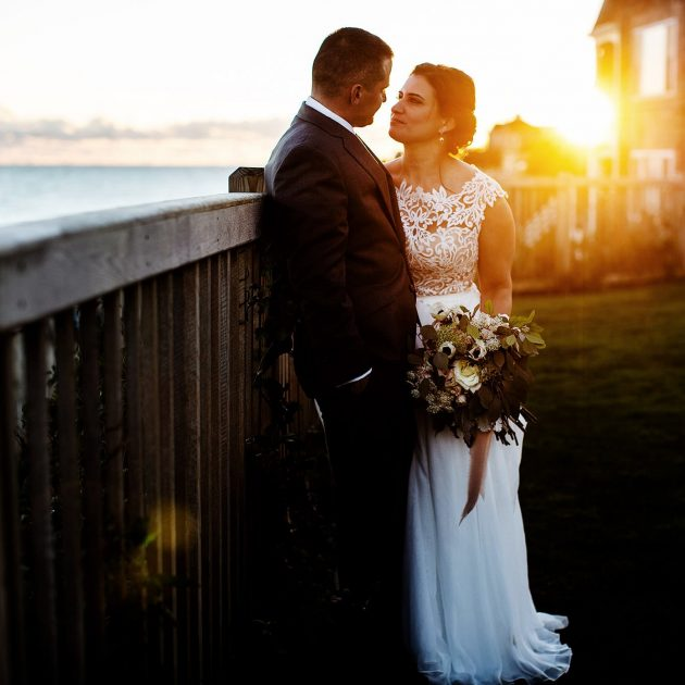 The bride and groom pose during sunset at Pelham House Resort in Dennisport, MA