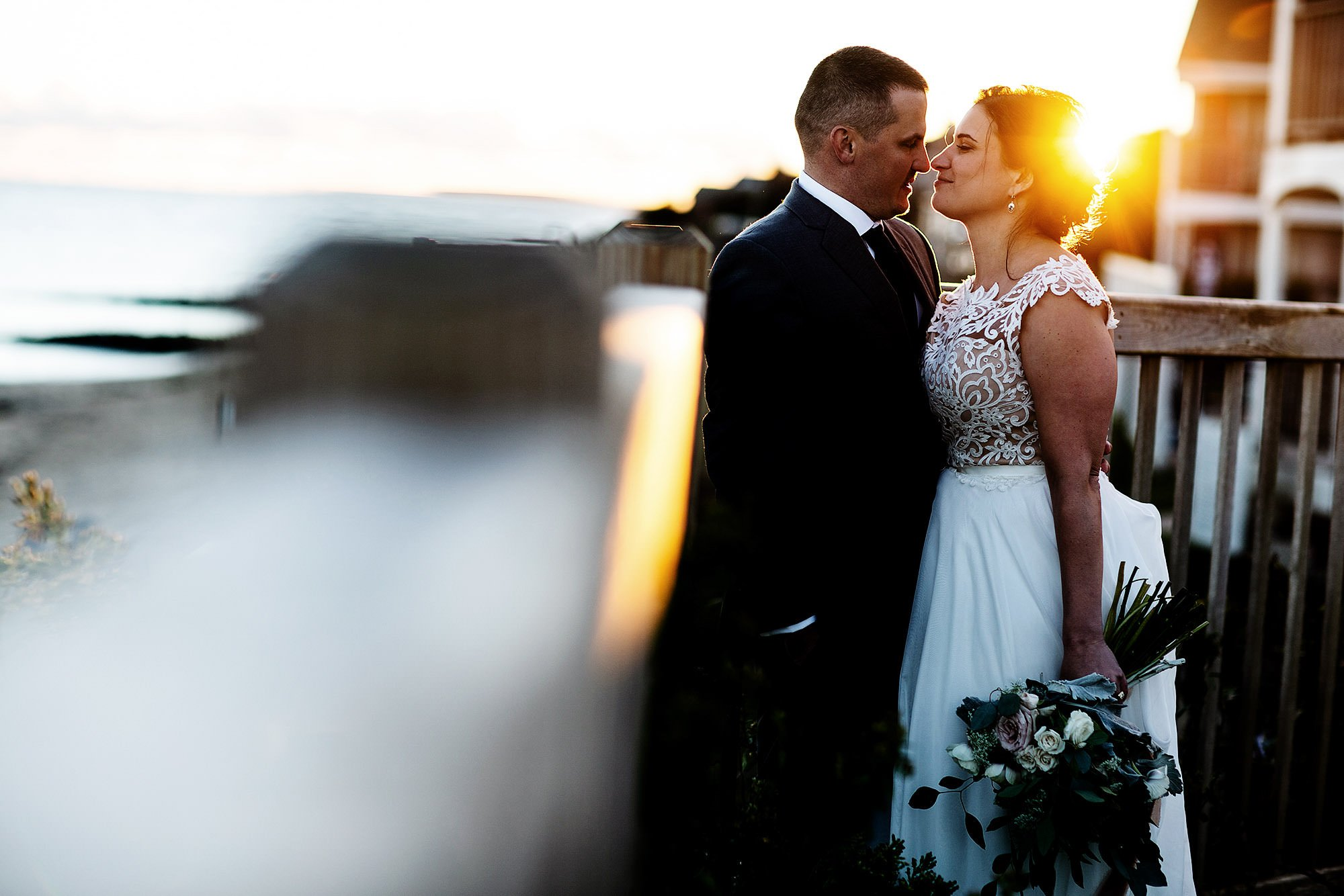 The bride and groom pose for a portrait at sunset during their Pelham House Resort wedding on Cape Cod.