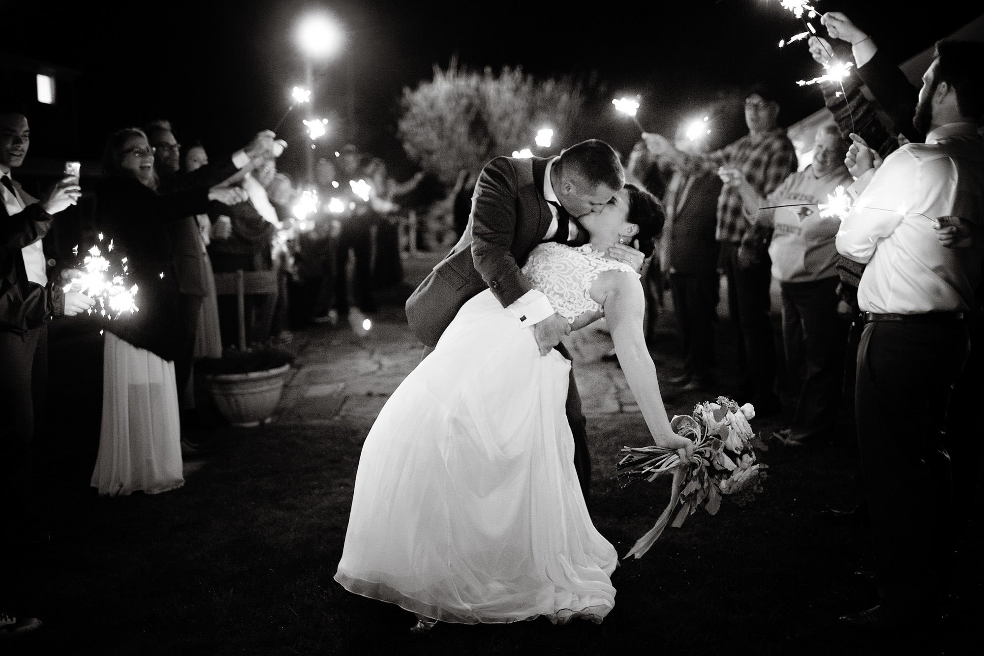 The couple kisses during a sparkler sendoff following their wedding reception at Pelham House Resort.