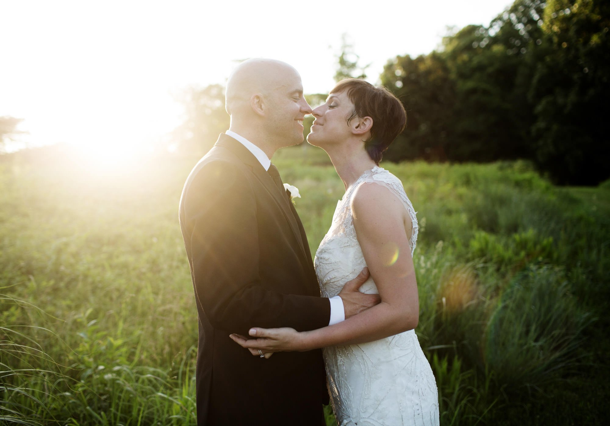 The bride and groom kiss during sunset on their River Farm wedding day.