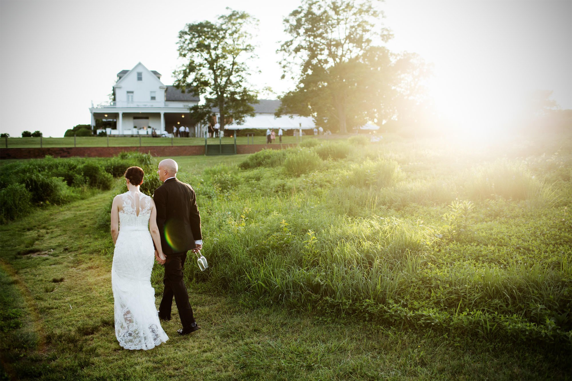 The bride and groom go for a walk during sunset on their River Farm wedding day.