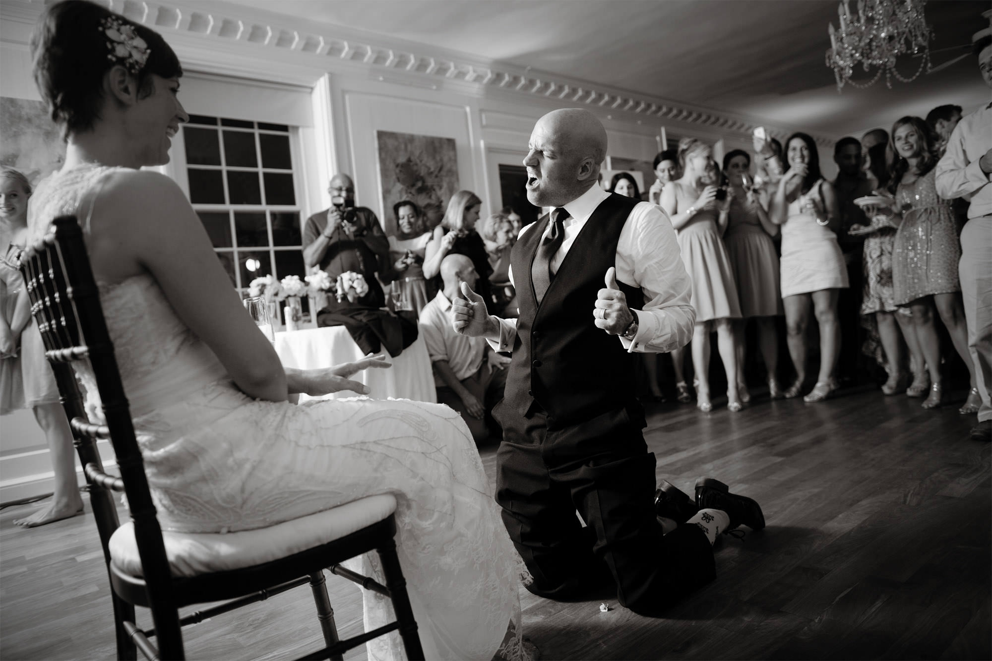 The groom prepares to remove the bride's garter during the wedding reception at River Farm.