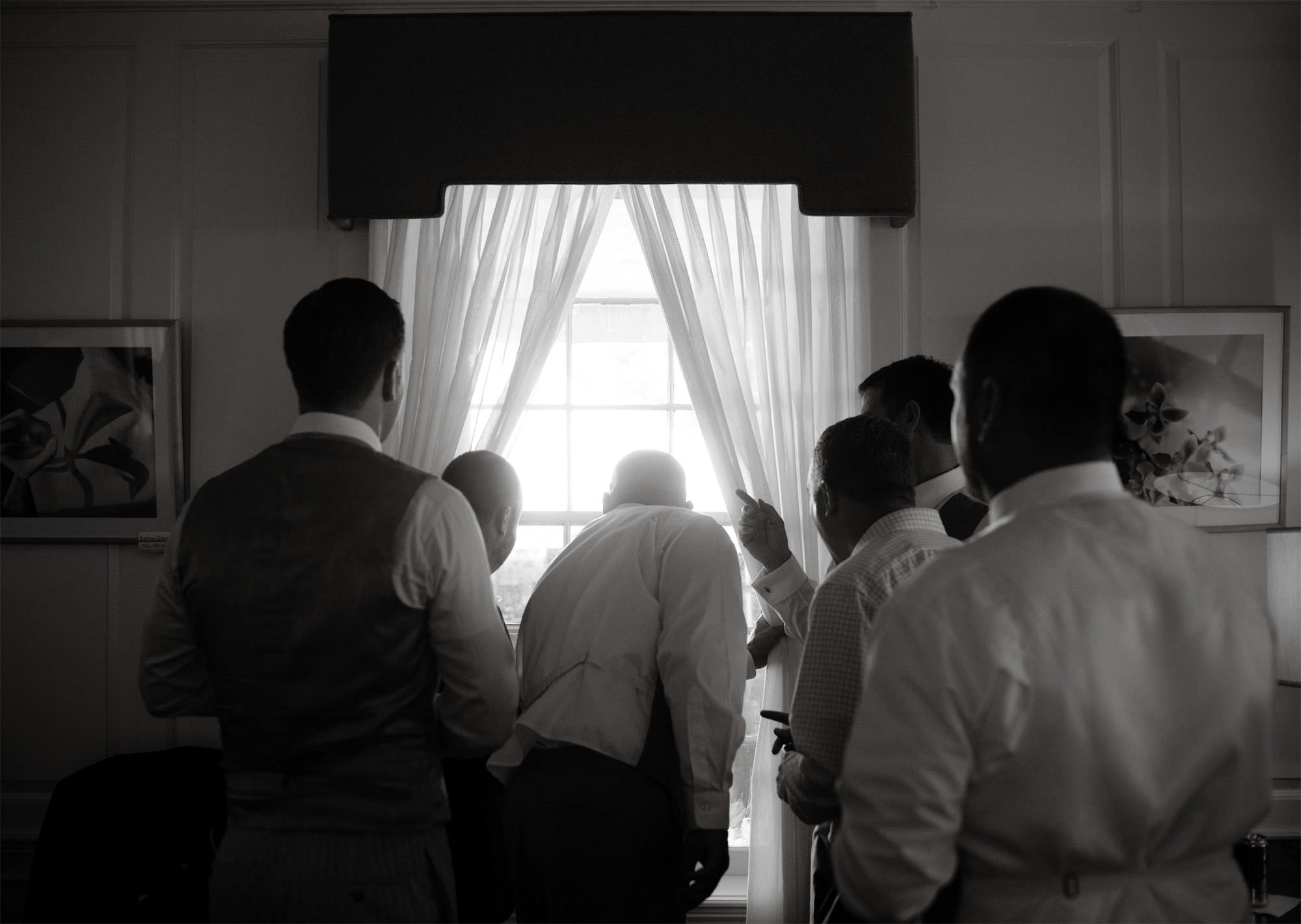 The groomsmen watch as guests arrive for the wedding ceremony at River Farm.