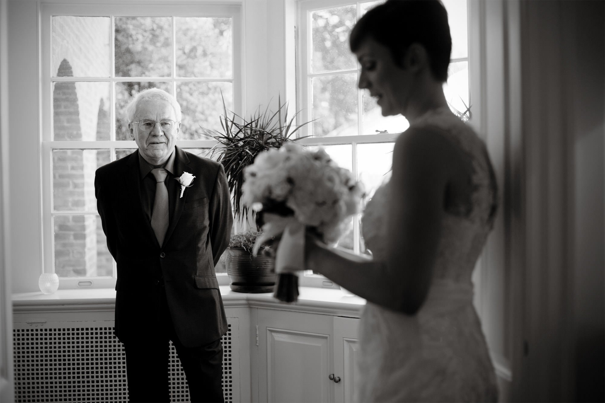 The bride and her father wait for the ceremony to begin during her River Farm wedding.