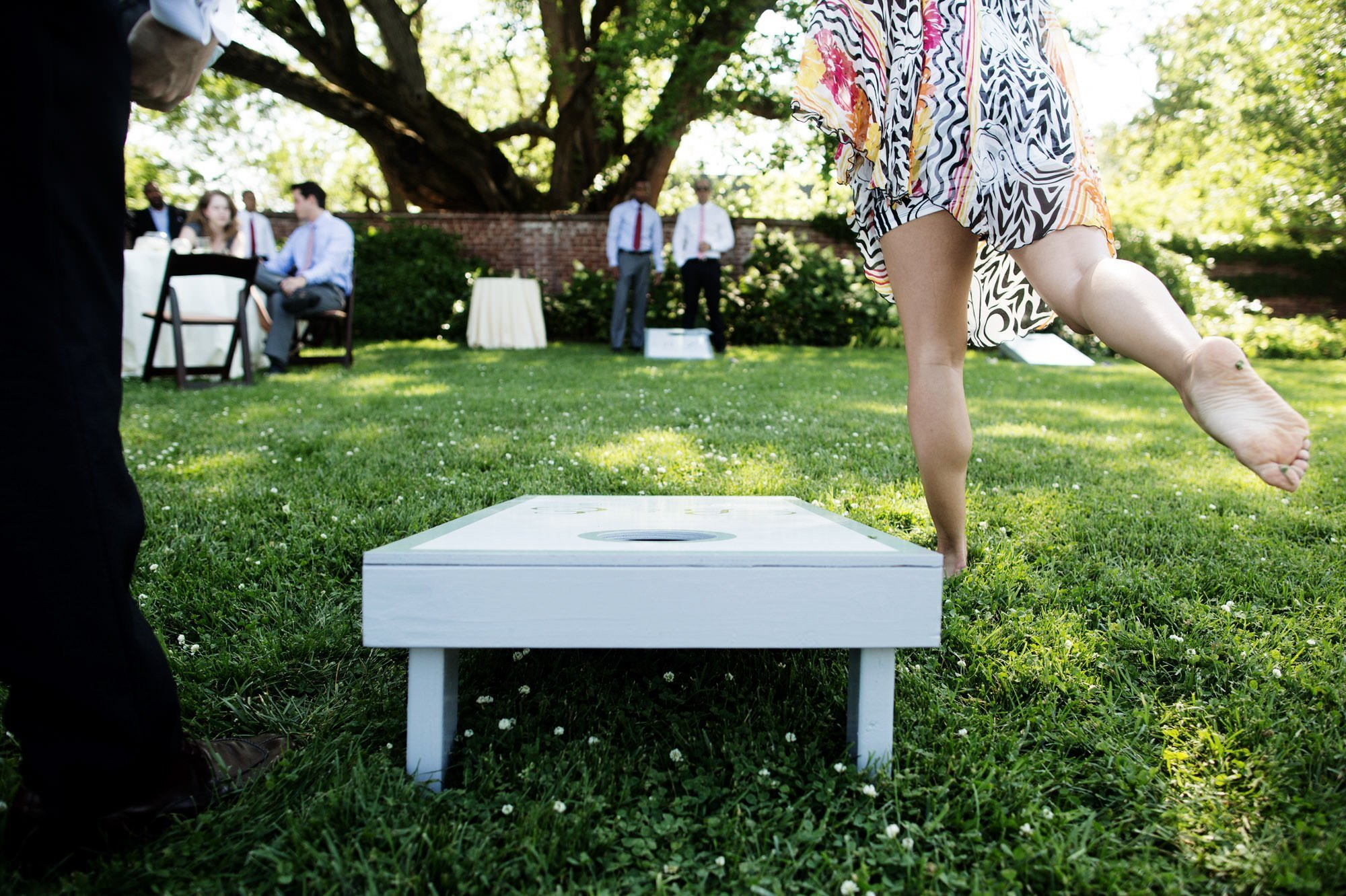 Guests play corn hole during cocktail hour during this River Farm wedding.