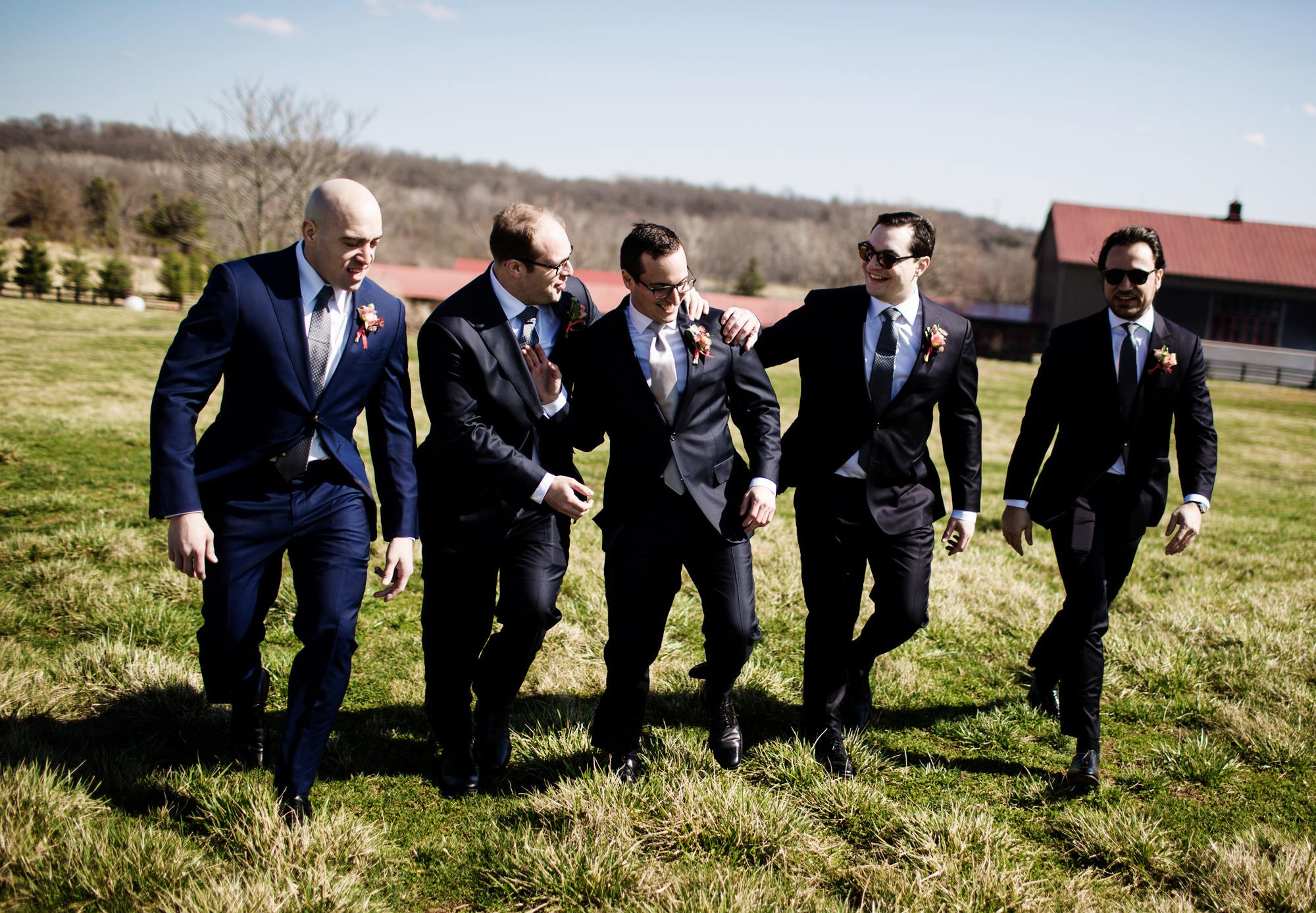 Riverside on the Potomac Wedding in Leesburg, VA  I  The grooms walks through a field with his groomsmen.