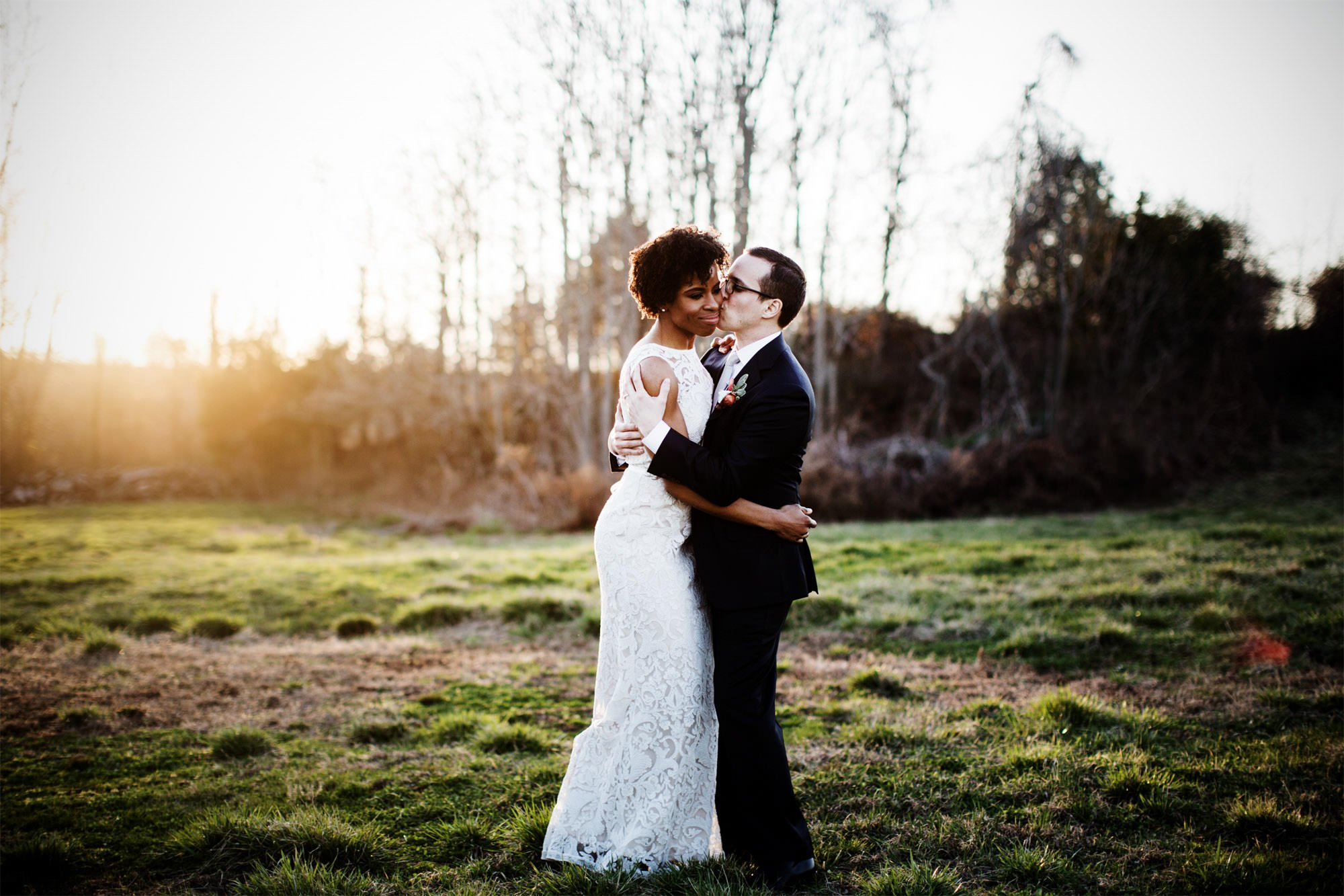 The bride and groom pose for a portrait at sunset during their Riverside on the Potomac wedding.