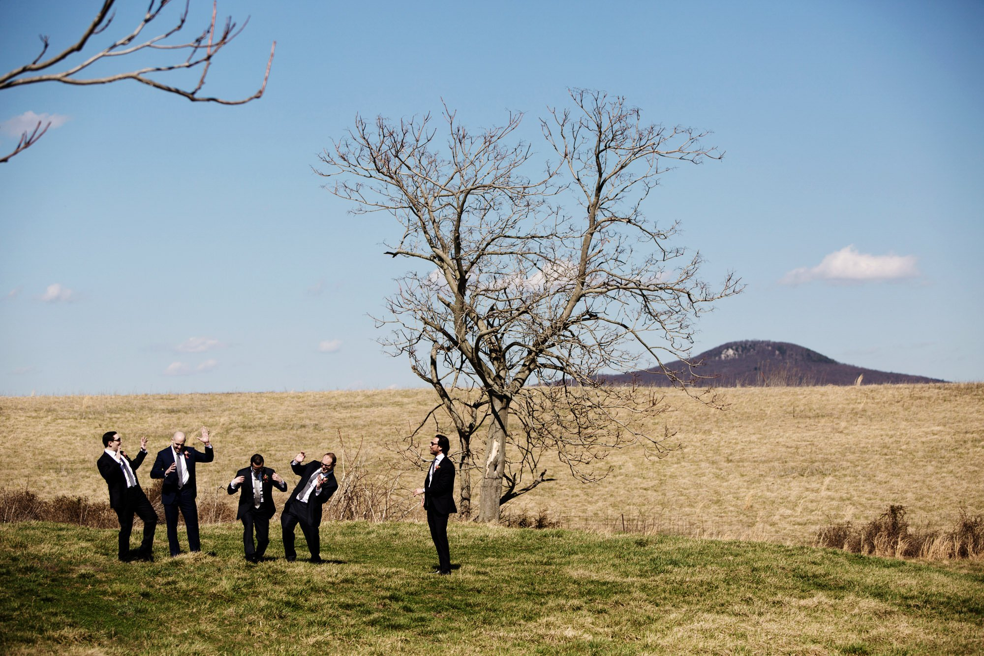 The groomsmen dance in an open field before the wedding ceremony.