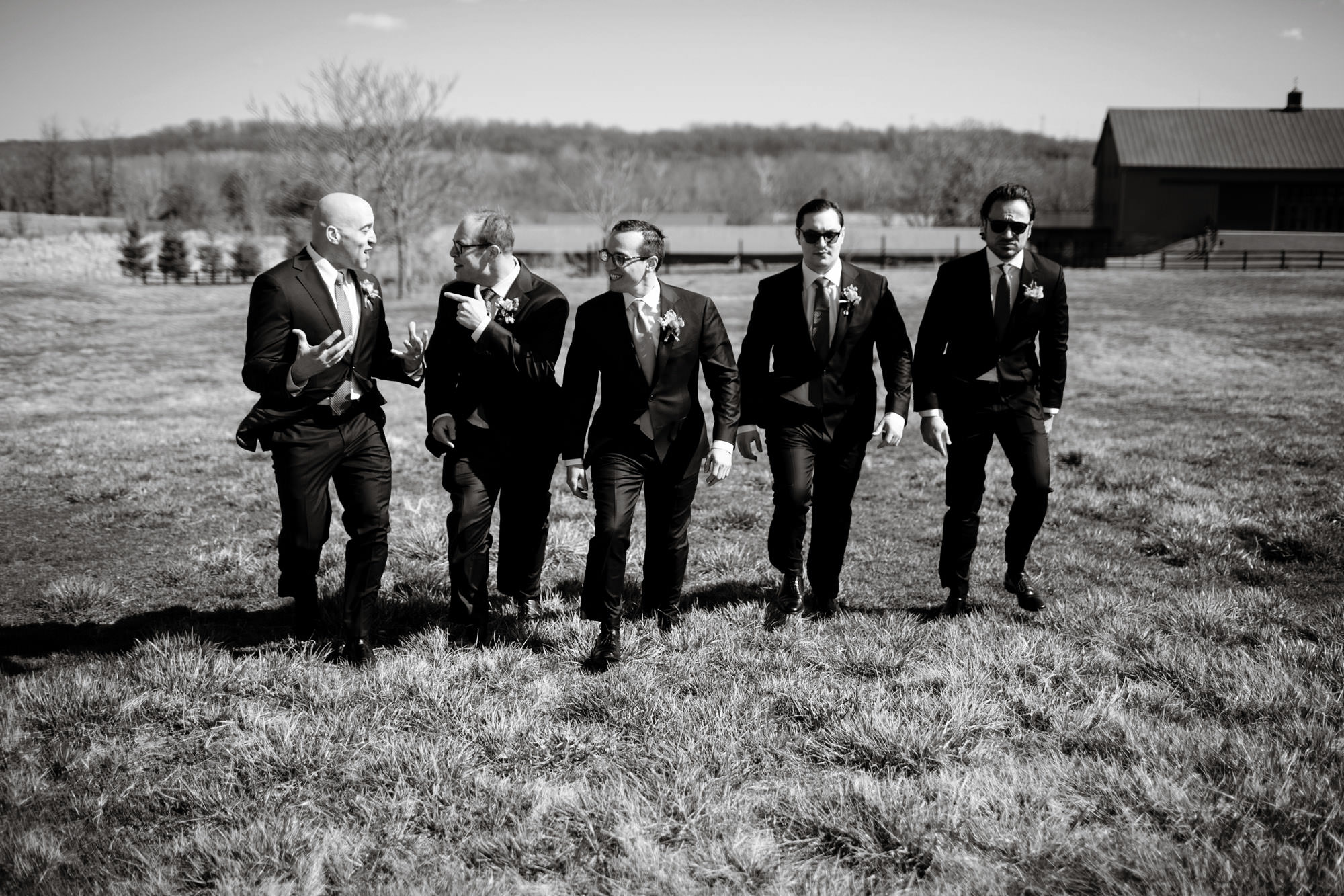 The groomsman walk through a field on the wedding day.