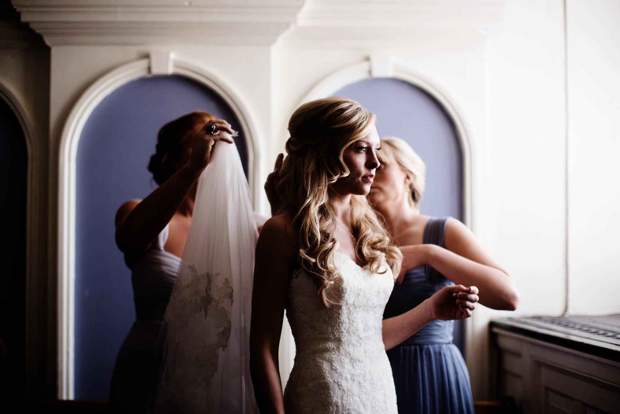 Bridesmaids help the bride put on her veil at St. Aloysius Gonzaga church.