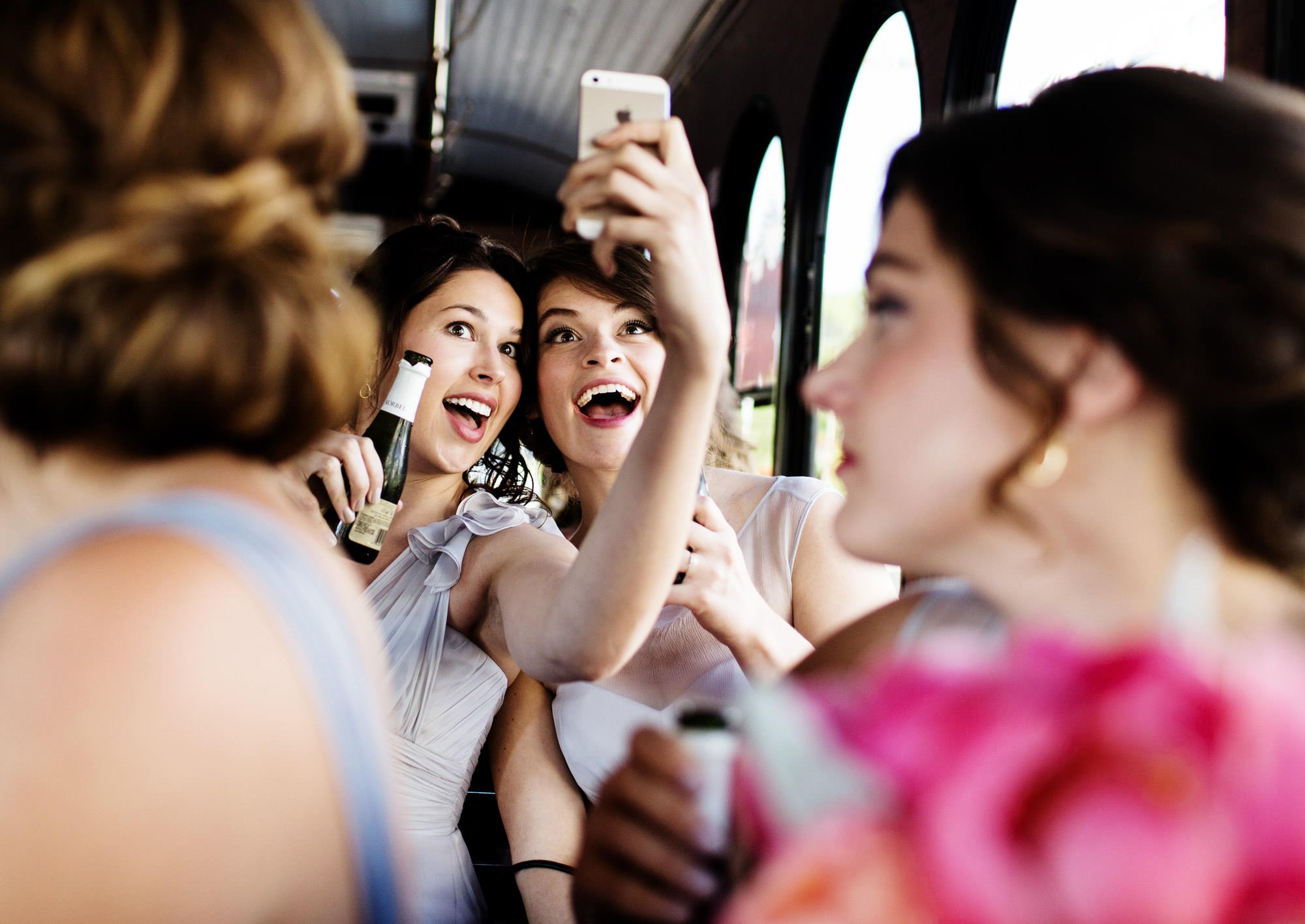 Bridesmaids take a selfie while riding a trolley to the wedding reception.