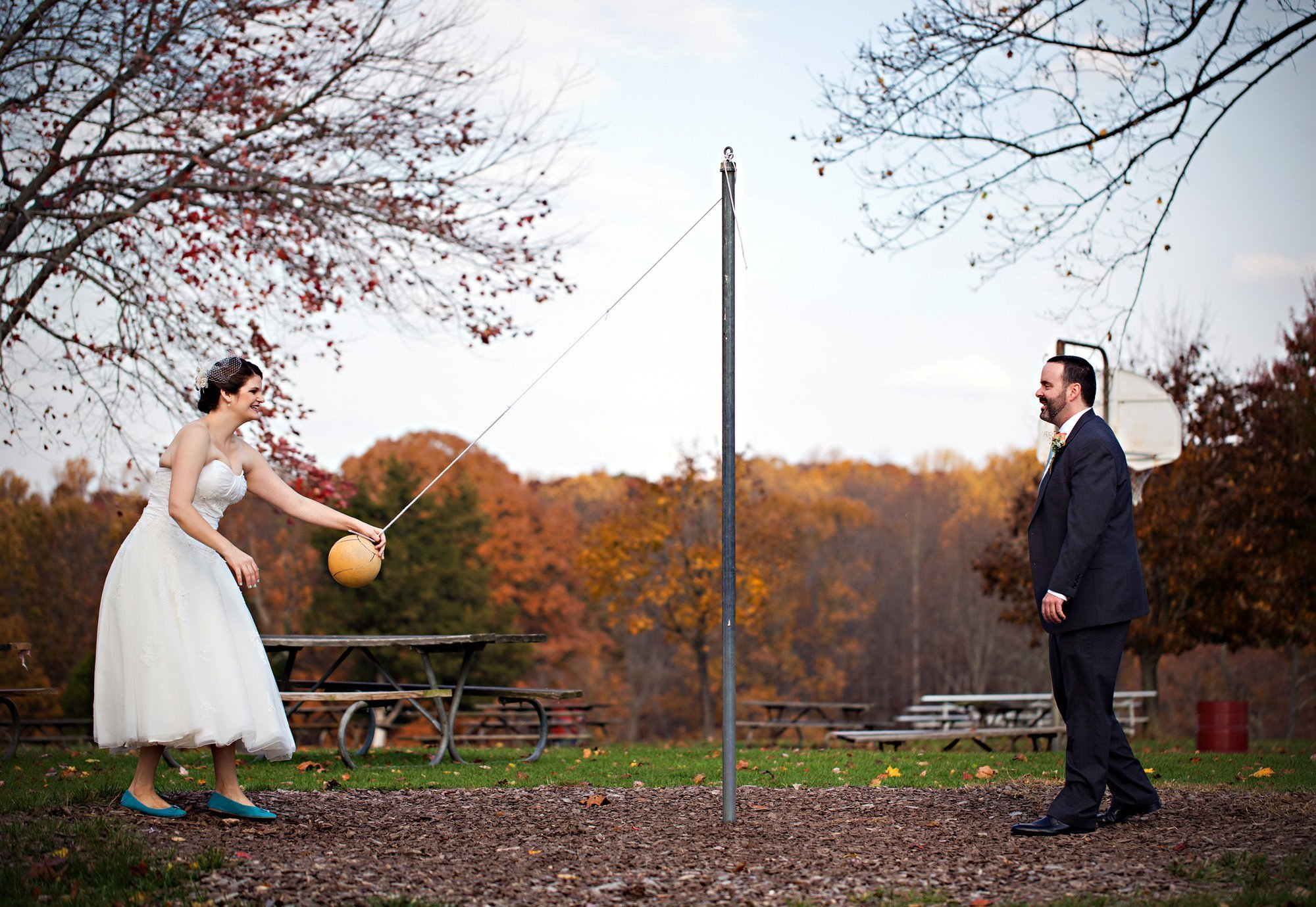 The bride and groom play tetherball after the ceremony during their Smokey Glen Farm wedding.