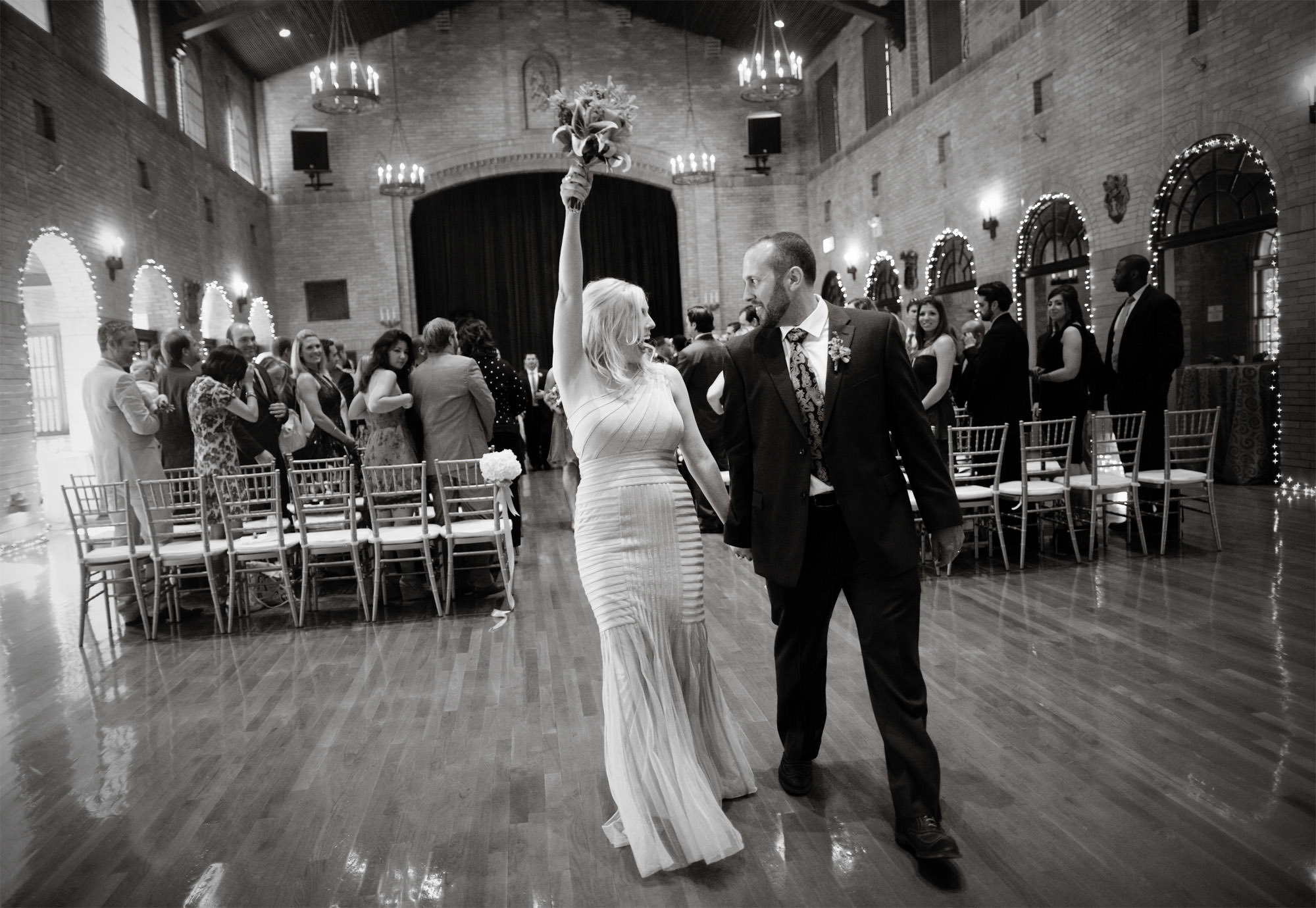 The bride and groom celebrate at the conclusion of their wedding ceremony at St Francis Hall.