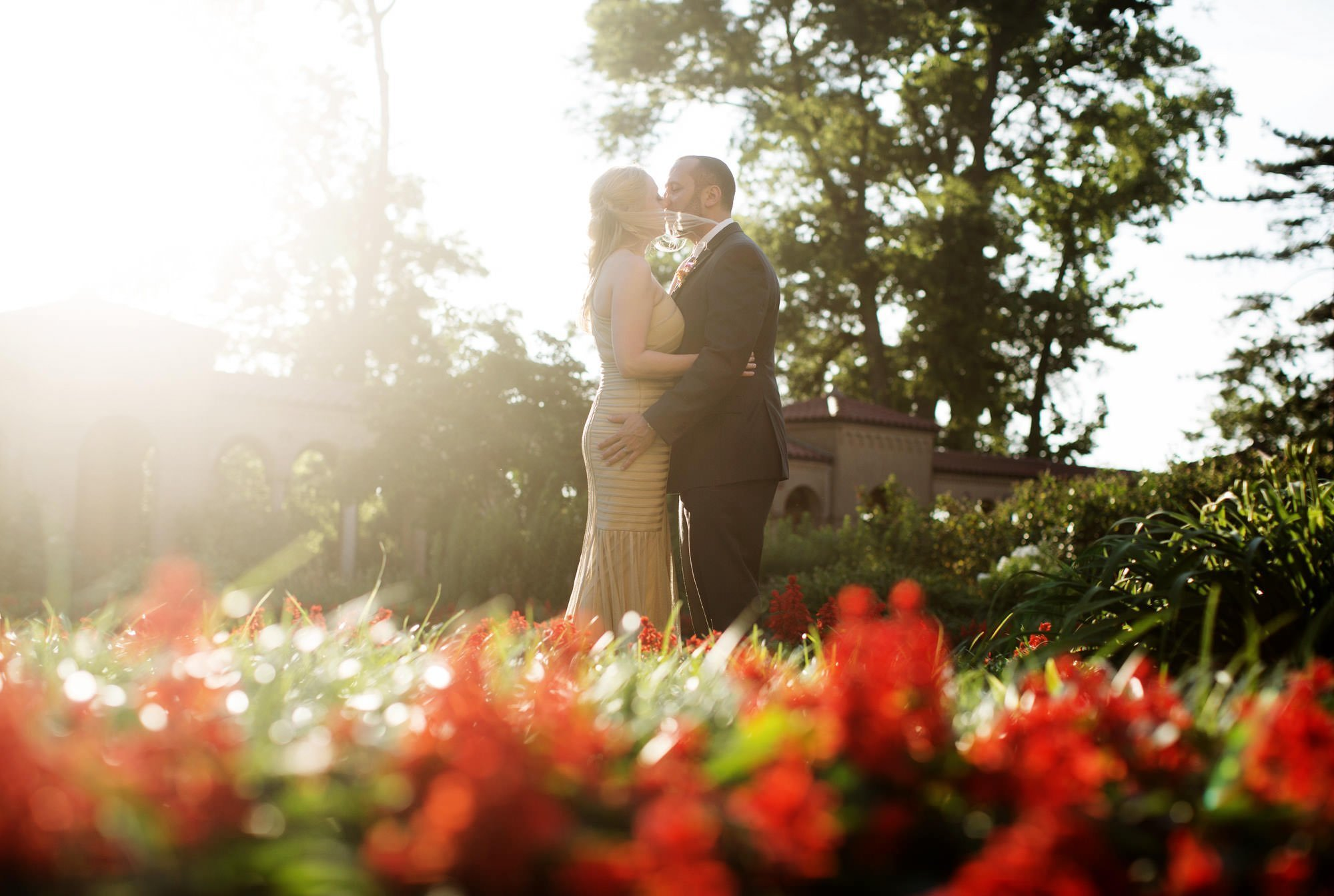 The couple kisses as the sun sets before their wedding at St Francis Hall.