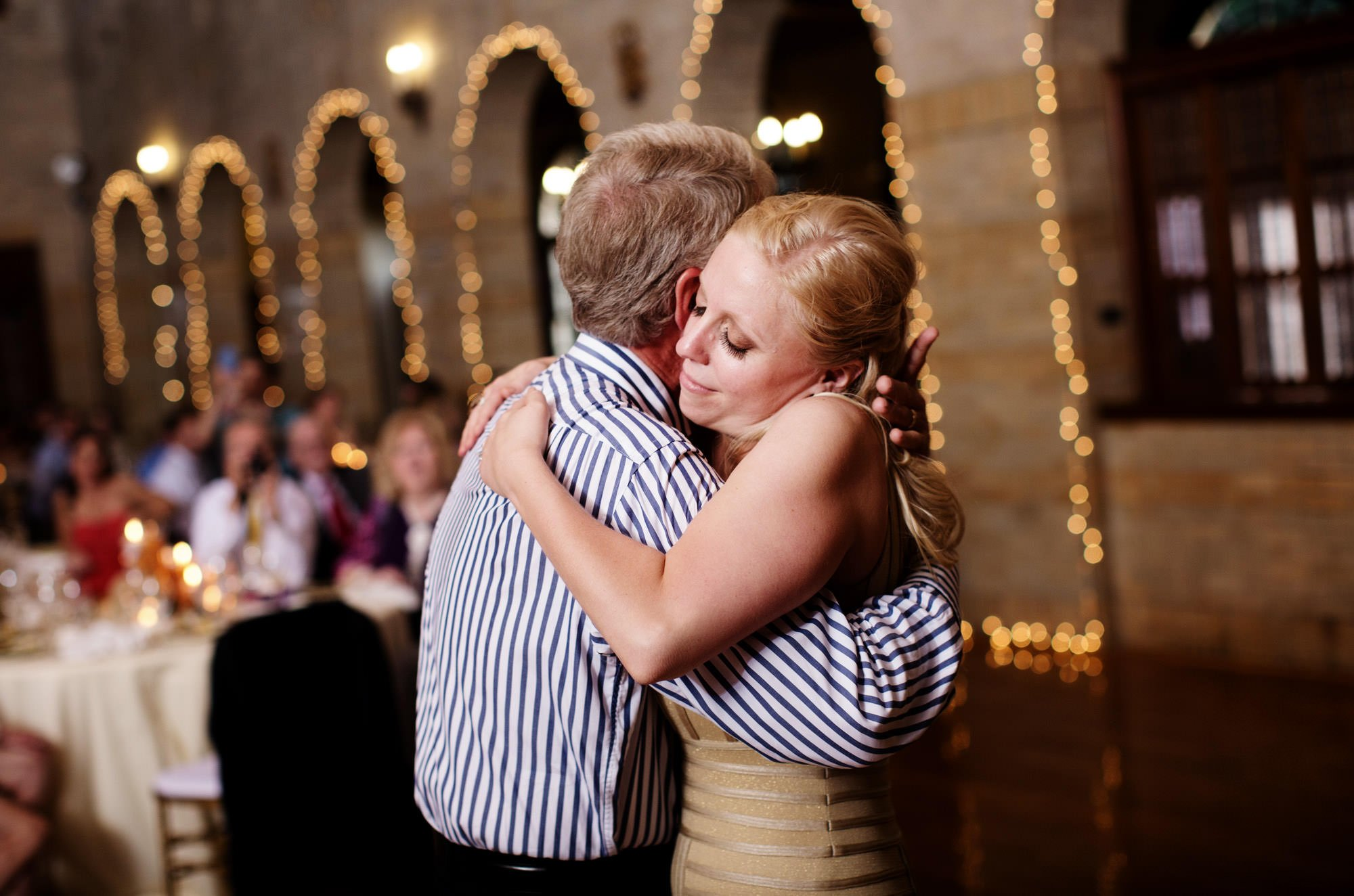 The bride hugs her father during the wedding reception at St Francis Hall.