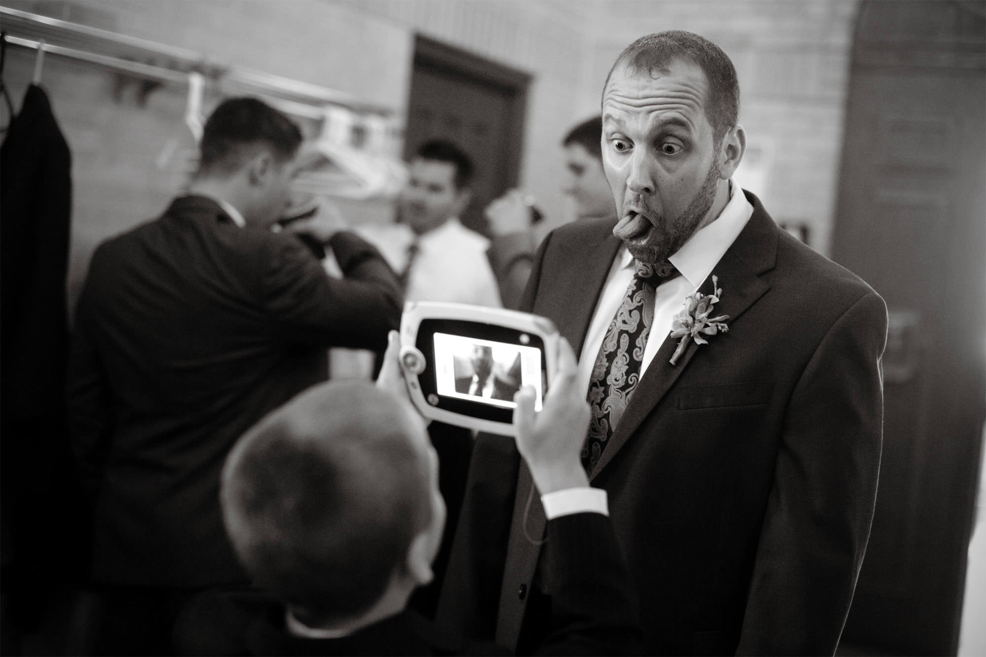 The groom makes a silly face before the wedding ceremony at St Francis Hall.