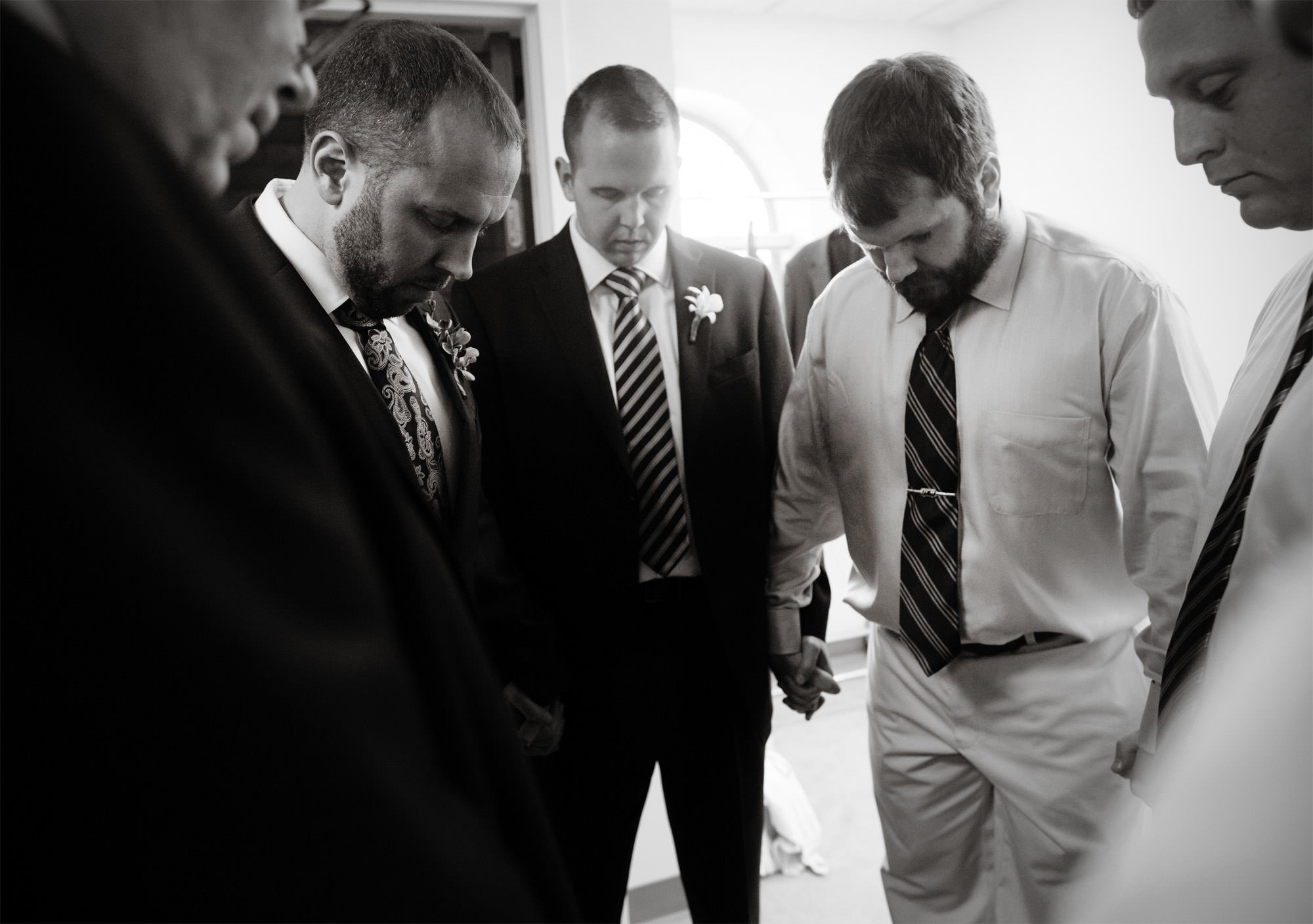 The groomsmen pray before the wedding ceremony at St Francis Hall.