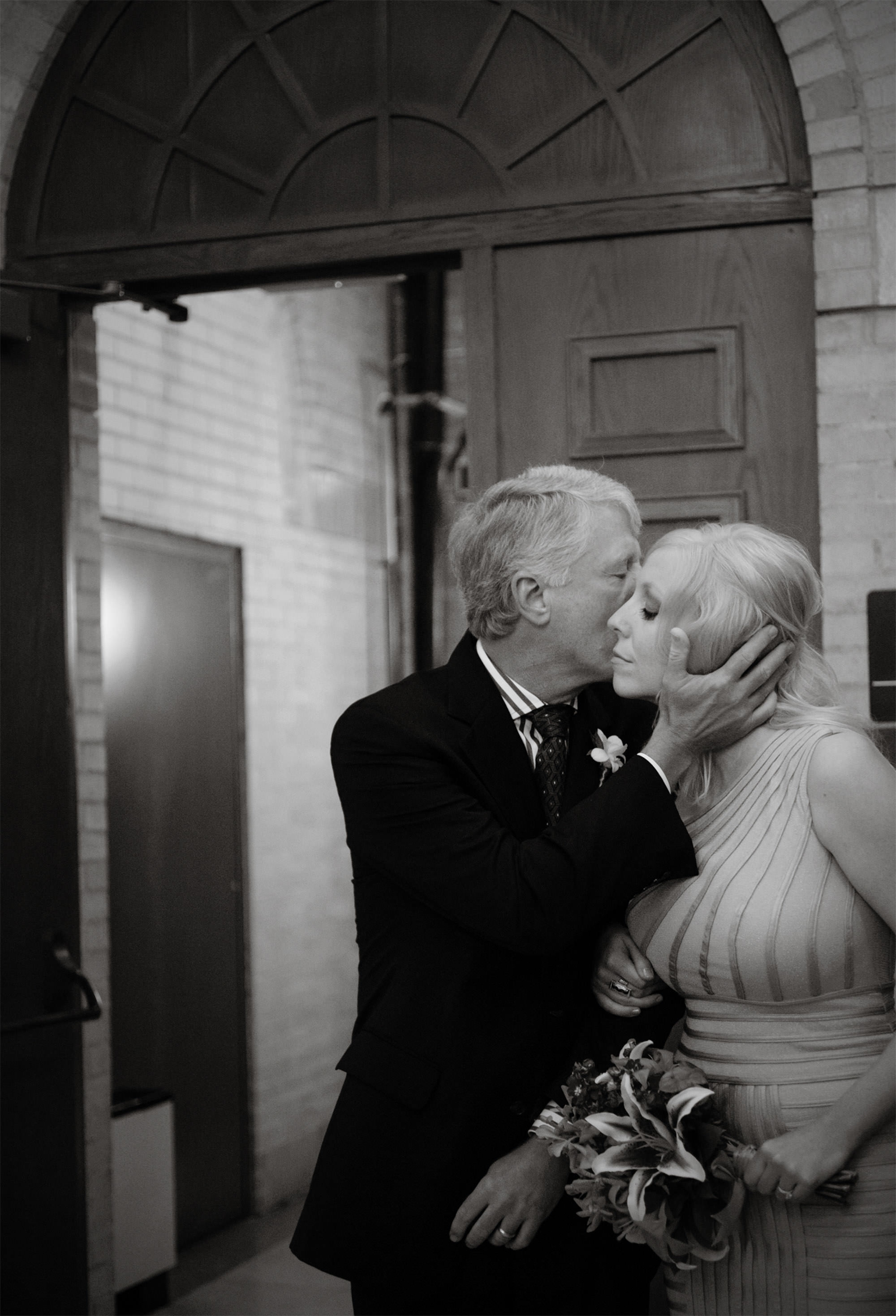 The bride is kissed by her father before the wedding ceremony at St Francis Hall.