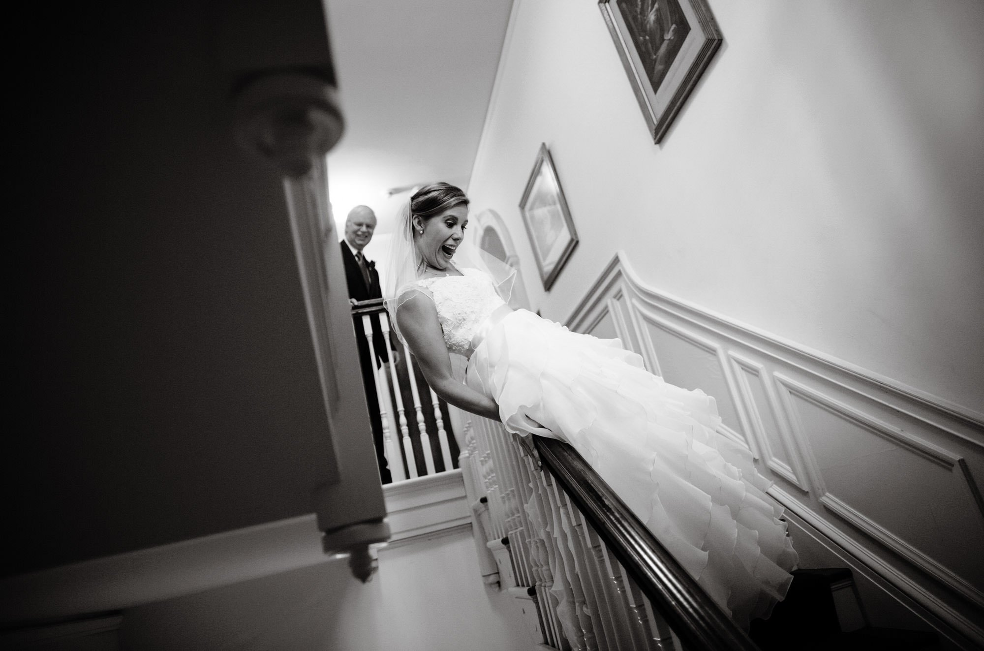 The bride slides down the bannister at Strong Mansion.