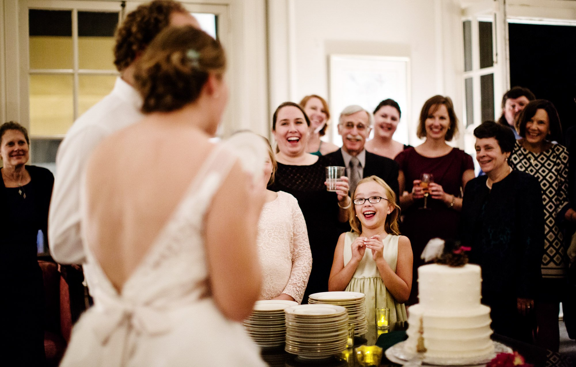 Guests watch the couple cut the wedding cake.