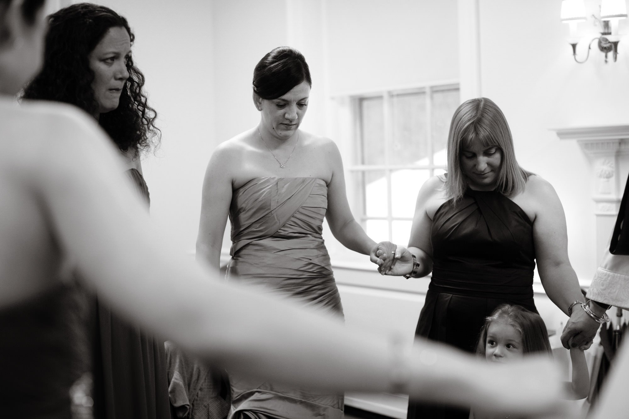 The bride prays with her bridesmaids before her wedding at Woodend Sanctuary.