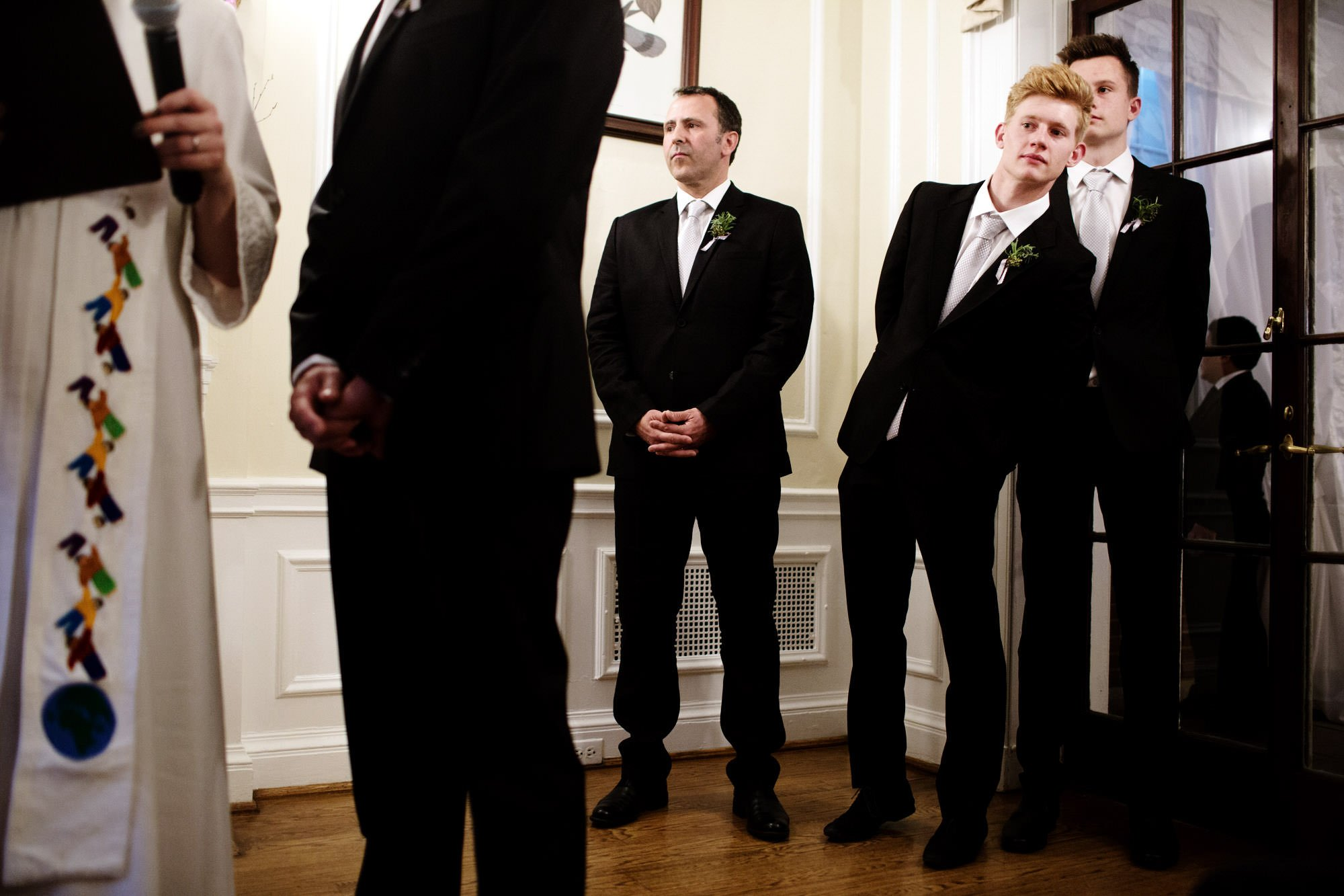 A groomsman watches the wedding ceremony.