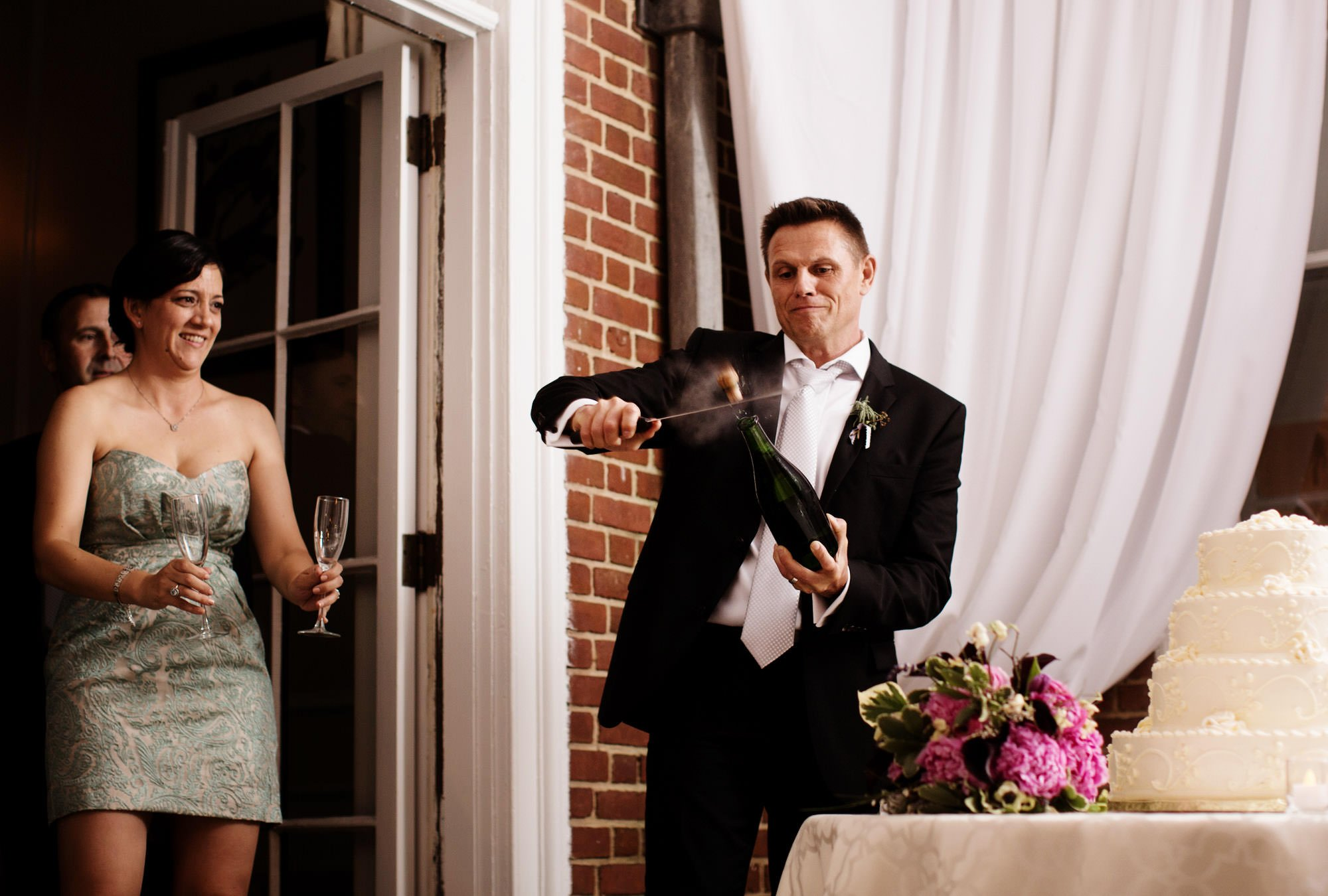 The groom pops the cork on a bottle of champaign during the wedding reception at Woodend Sanctuary.