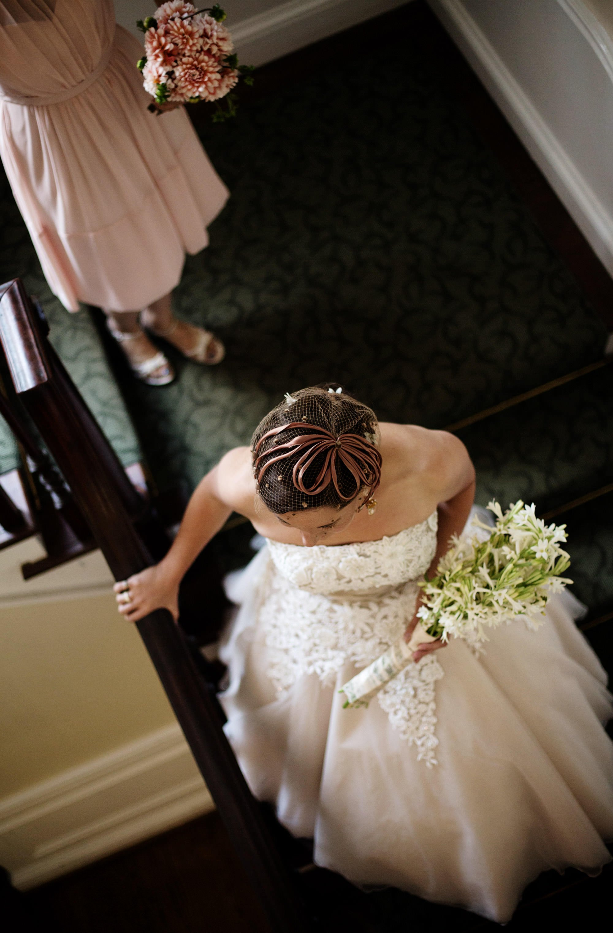 The bride walks down the staircase during her Woodend Sanctuary and Mansion Wedding.