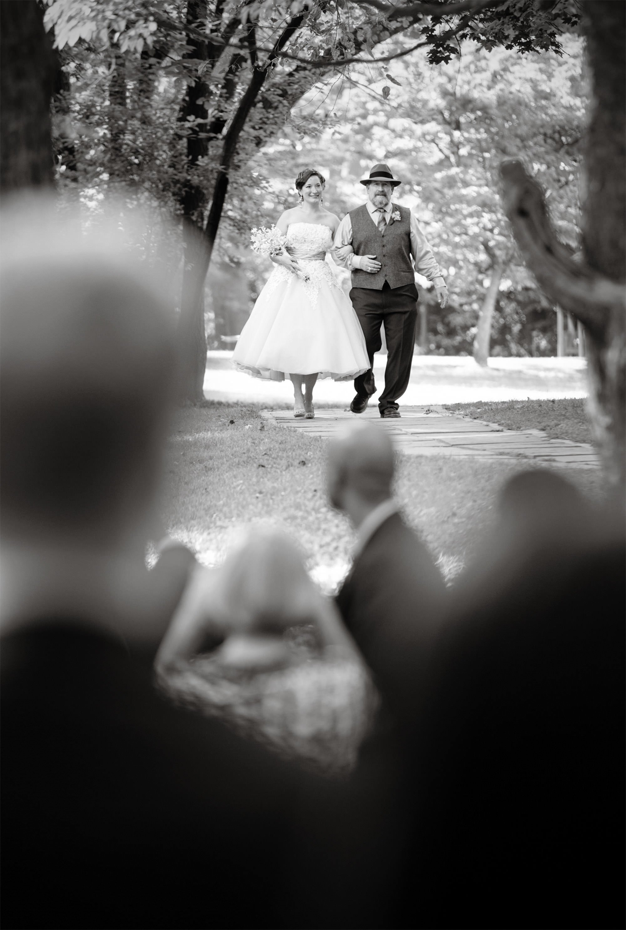 The bride is escorted toward the ceremony site during her Woodend Sanctuary and Mansion Wedding.