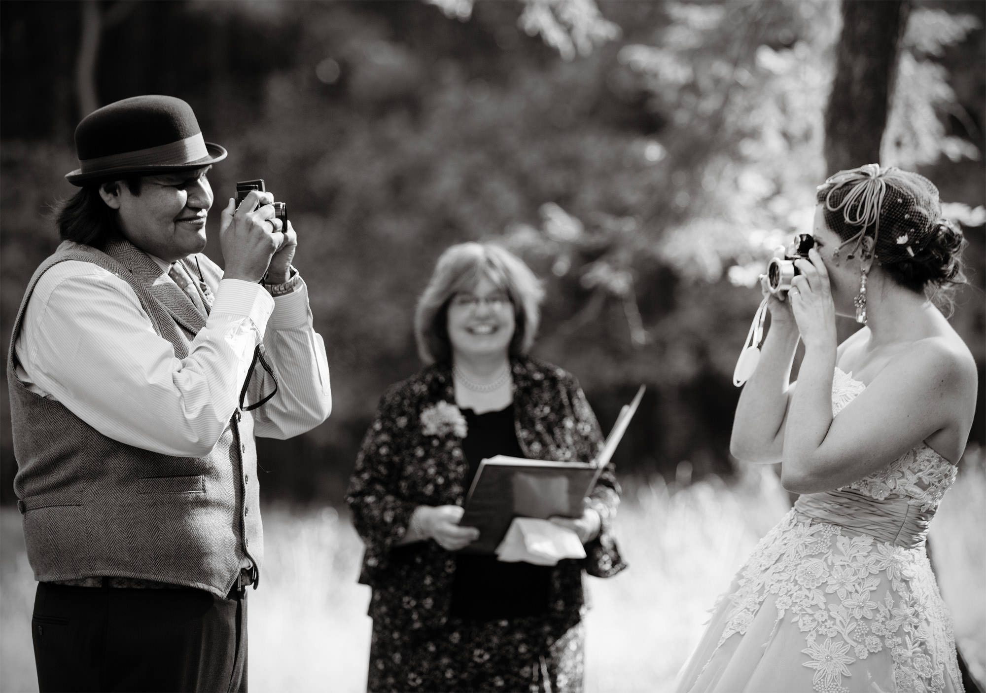 The couple takes pictures of each other during their wedding ceremony at Woodend Sanctuary and Mansion.