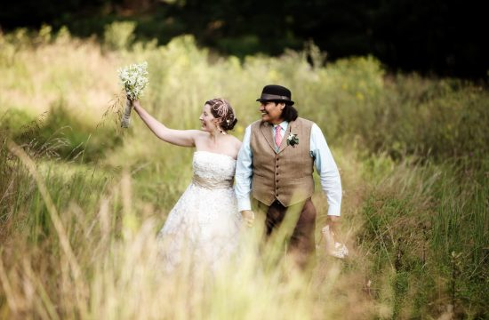 Woodend Sanctuary Weddings I The bride and groom walk through a grassy field at sunset.