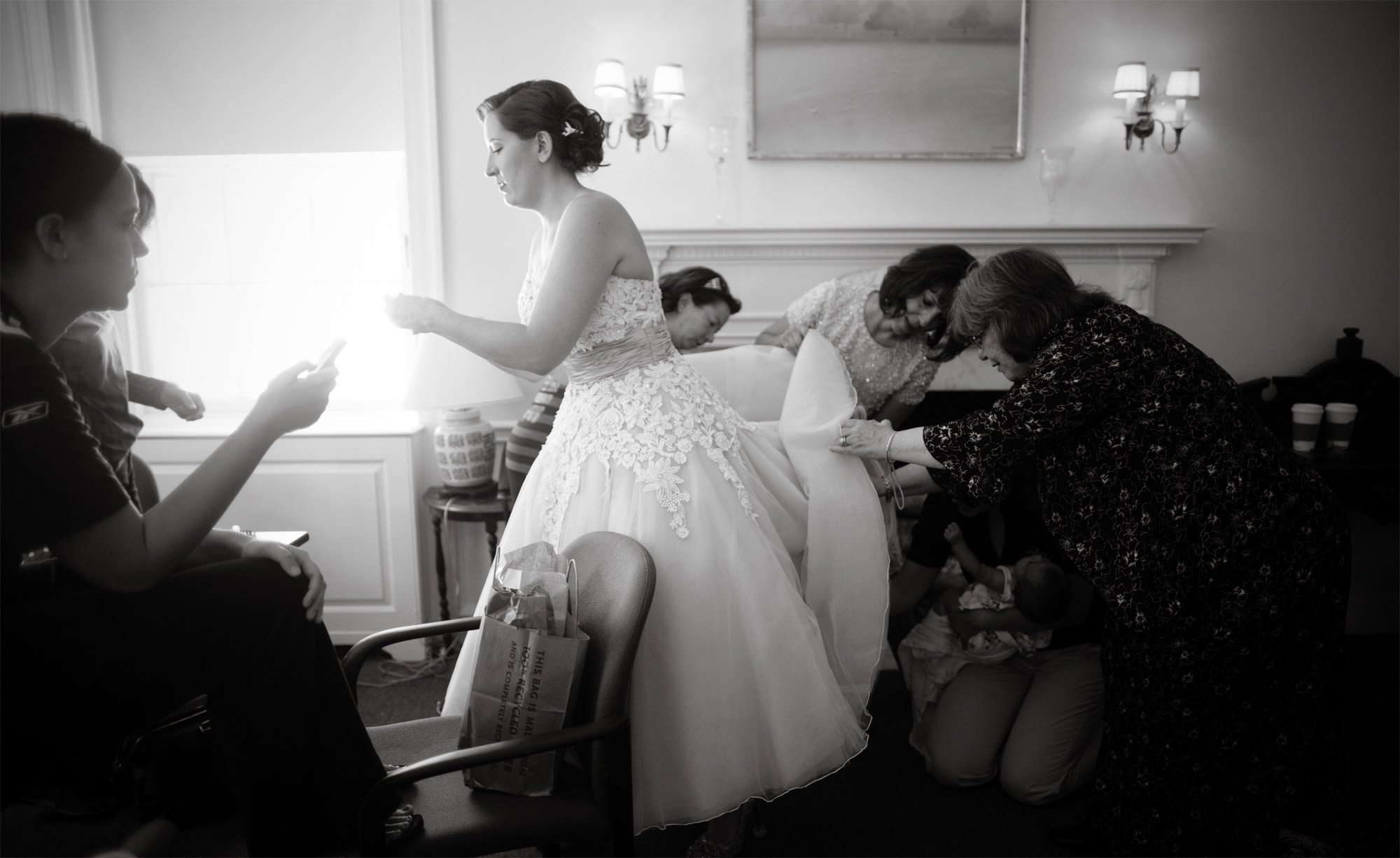 The bride is helped with her wedding dress prior to her Woodend Sanctuary and Mansion Wedding.