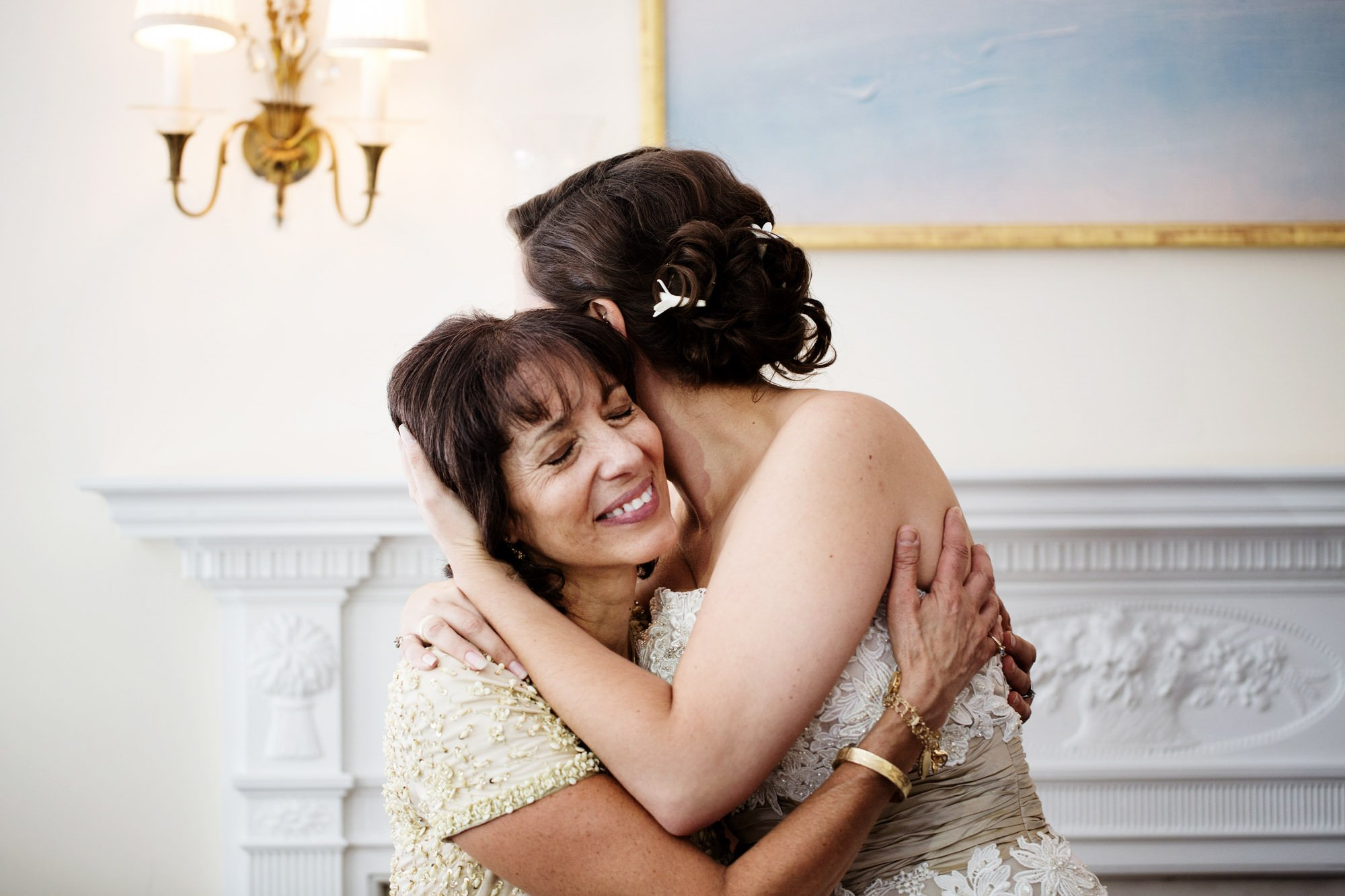 The mother of the bride hugs her daughter on her Woodend Sanctuary and Mansion Wedding day.