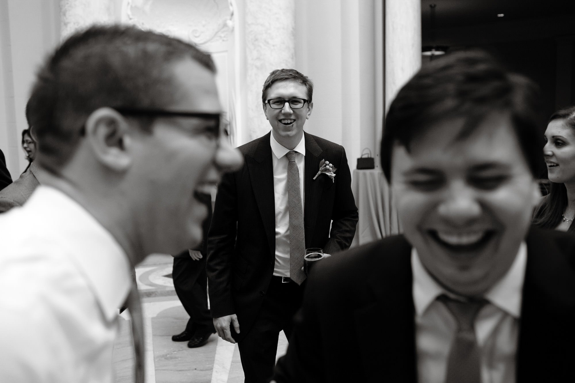 The groom laughs with friends during the Carnegie Institute for Science Wedding reception.