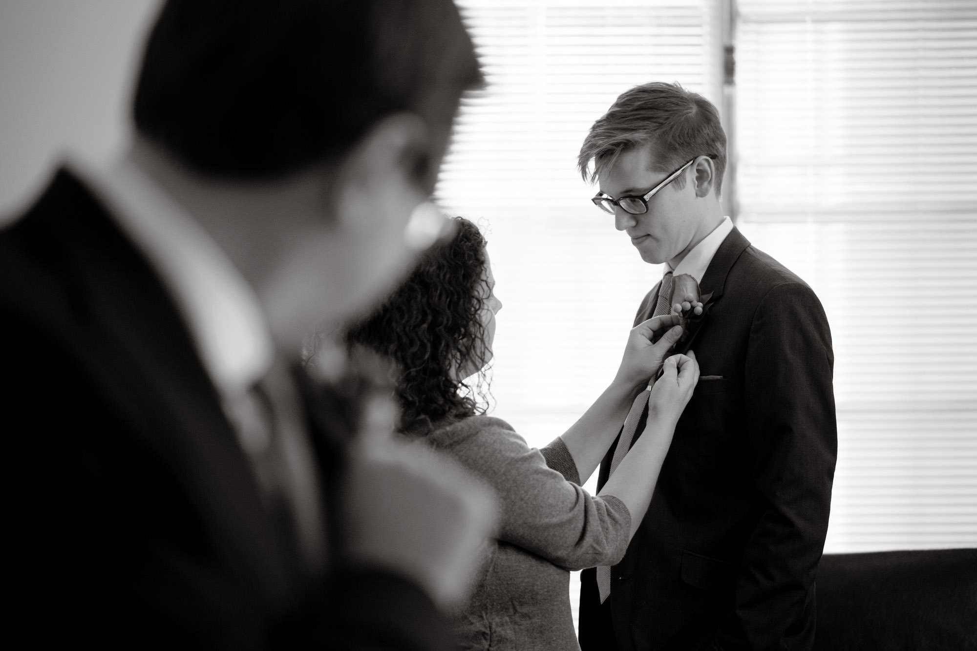 A groomsman puts on his boutonniere on the Carnegie Institute for Science Wedding day.
