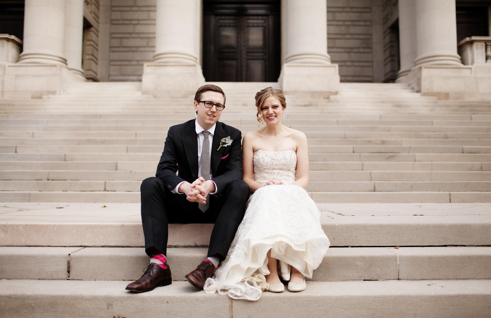 The bride and groom pose for a portrait on the steps of the Carnegie Institute for Science.