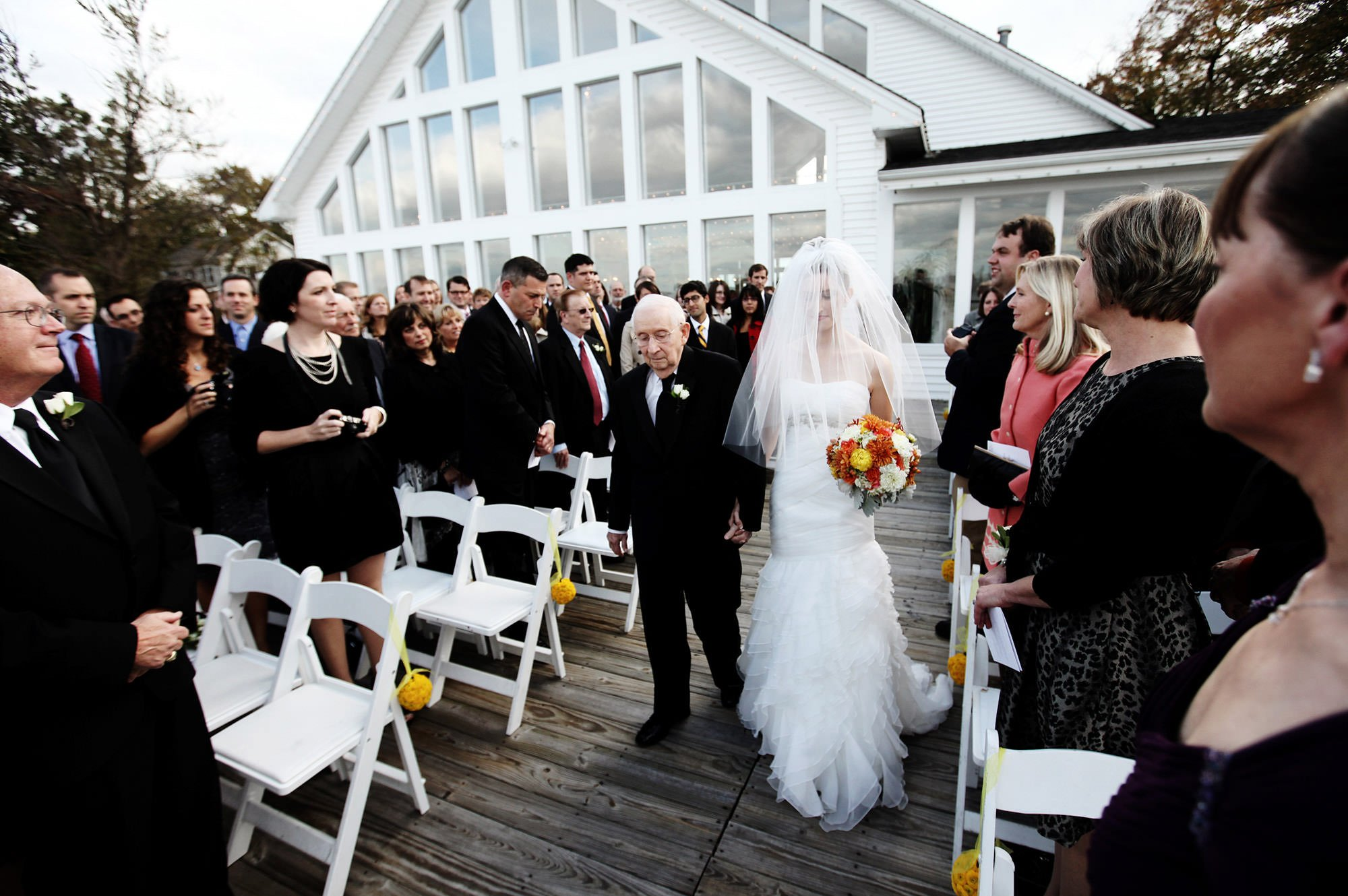 The bride is escorted down the aisle during her Celebrations at the Bay wedding ceremony.