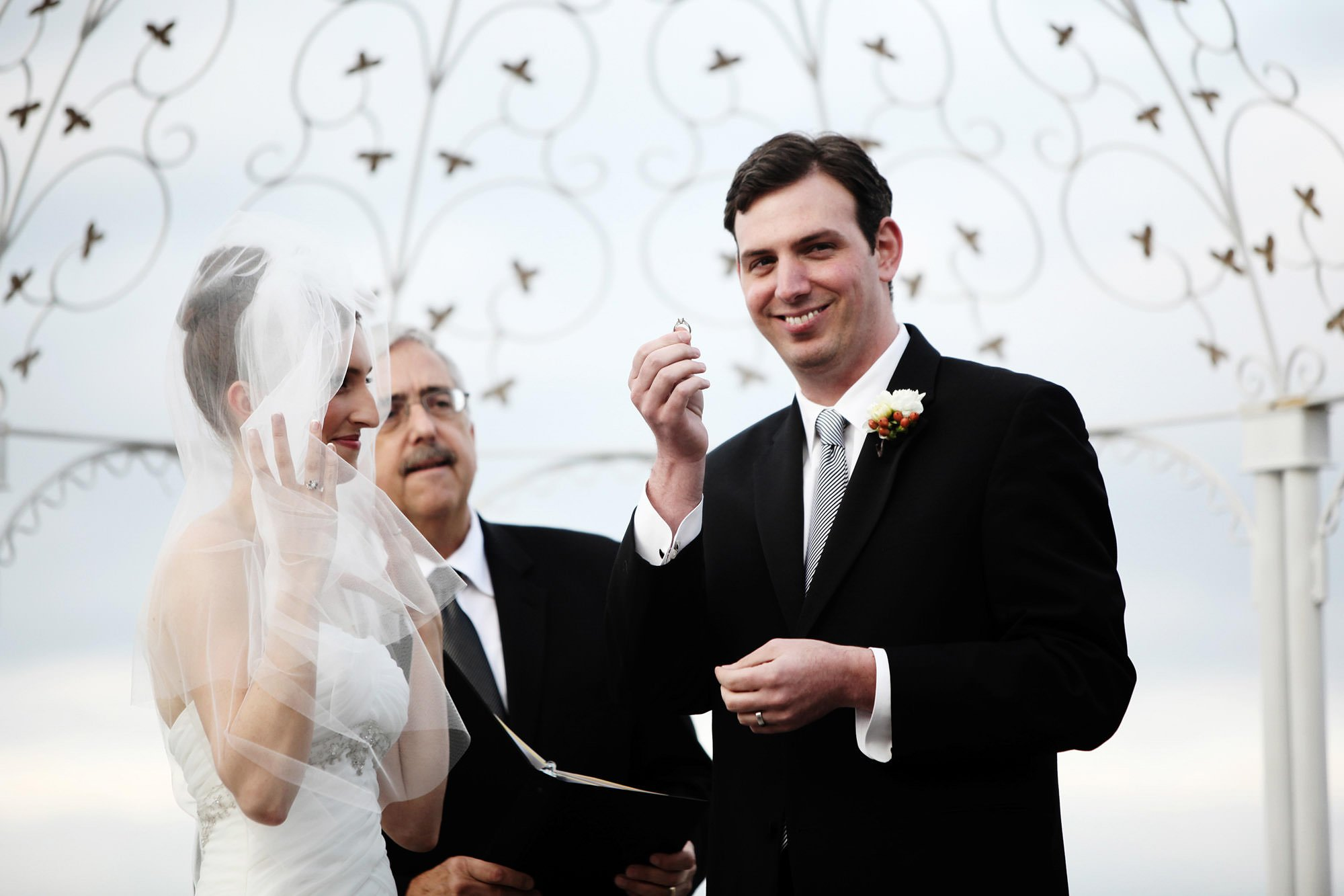The groom holds up the wedding ring during the Celebrations at the Bay wedding ceremony.