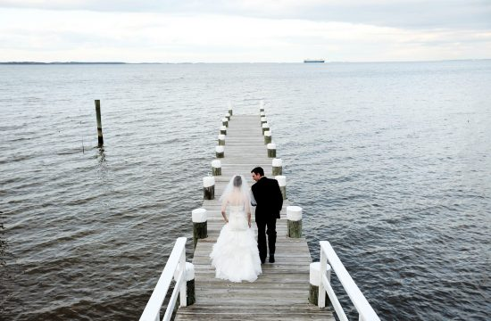 The bride and groom walk down the dock during their Celebrations at the Bay wedding in Pasadena, MD.