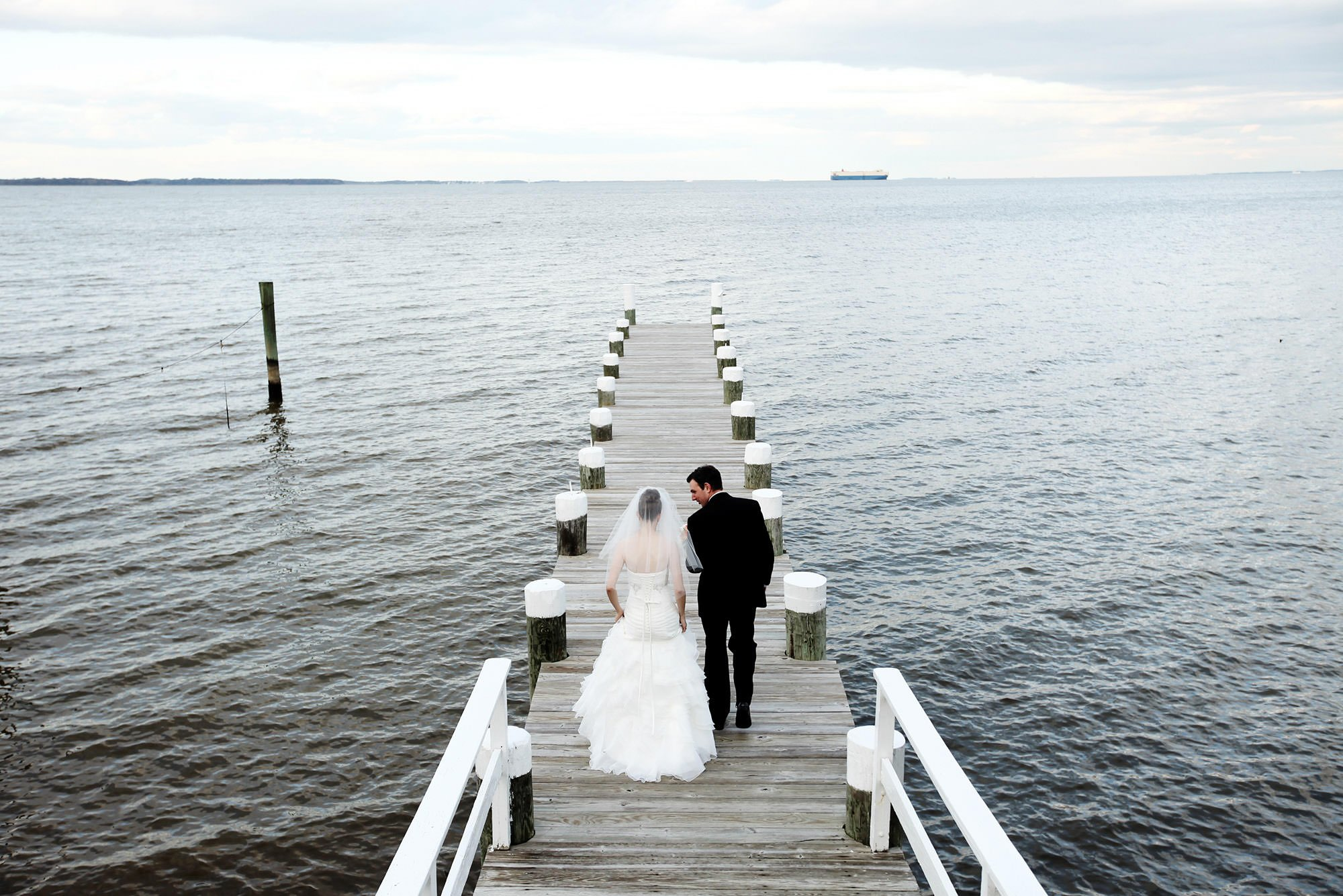 The couple walks down the dock during their Celebrations at the Bay wedding.