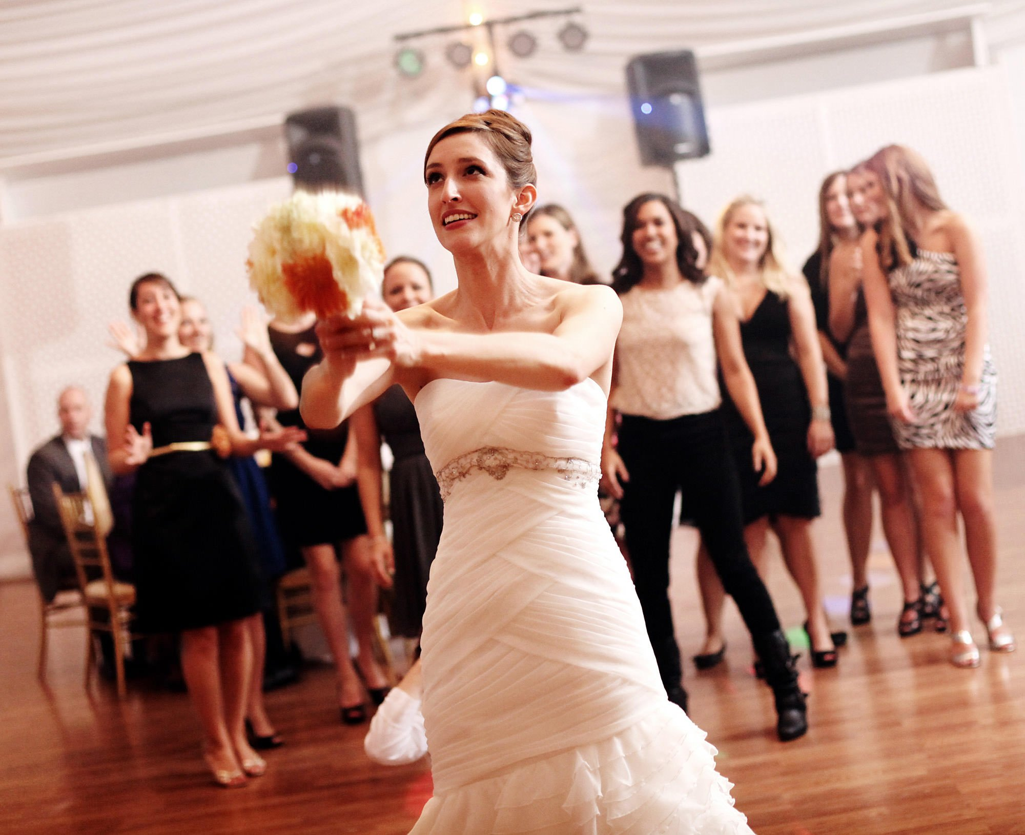 The bride tosses her bouquet during the wedding reception at Celebrations at the Bay.