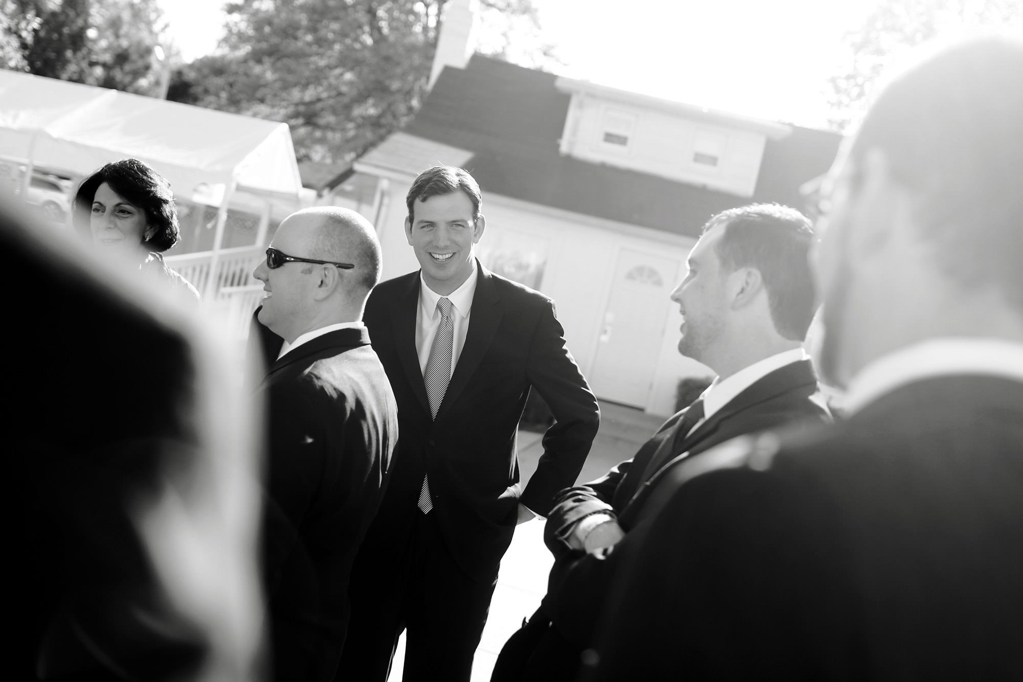 The groom laughs with his groomsmen before the wedding ceremony at Celebrations at the Bay.